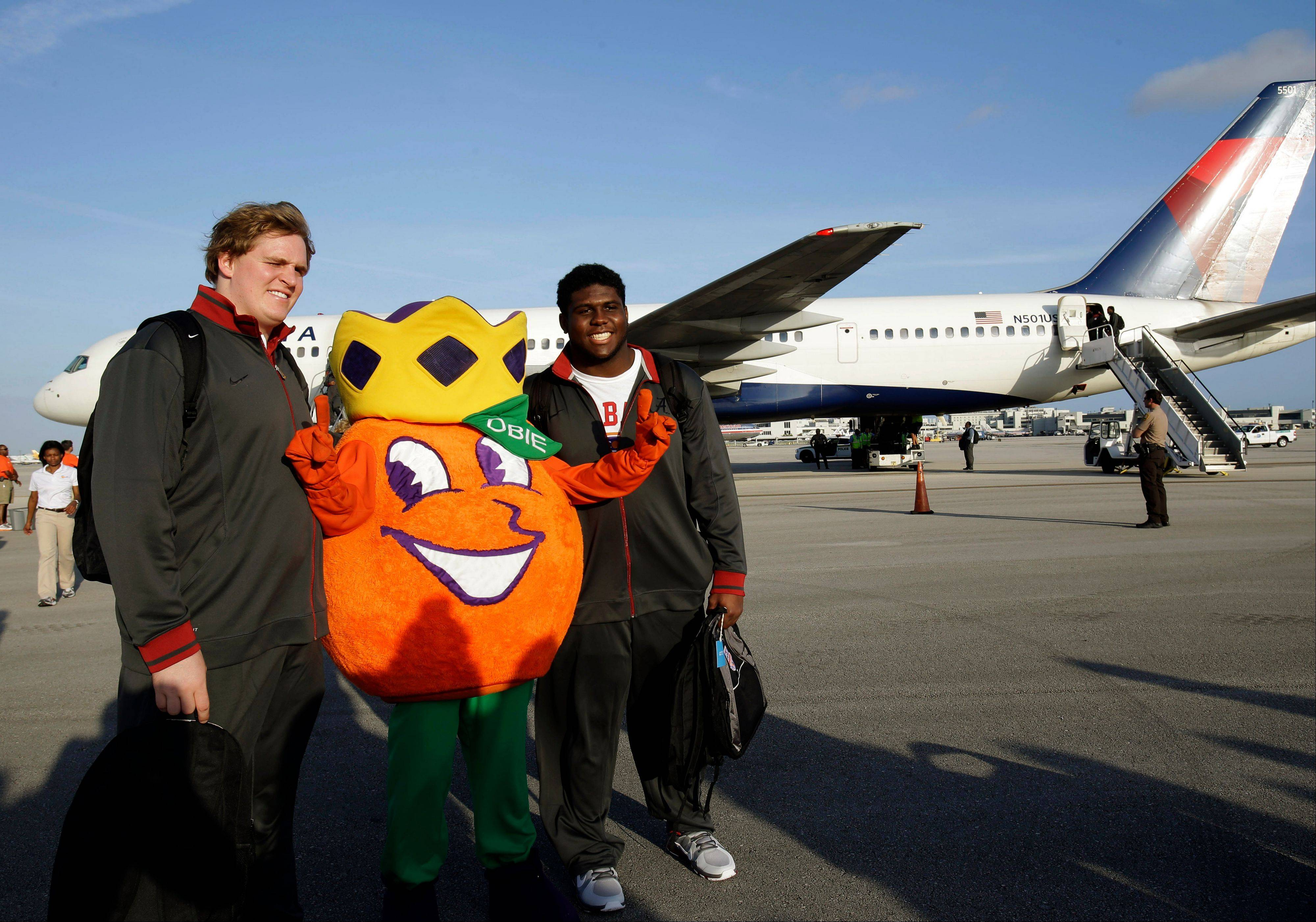 Alabama's Barrett Jones, left, and Chance Warmack, right, pose with Obie, the Orange Bowl Committee mascot, Wednesday upon arriving at Miami International Airport.