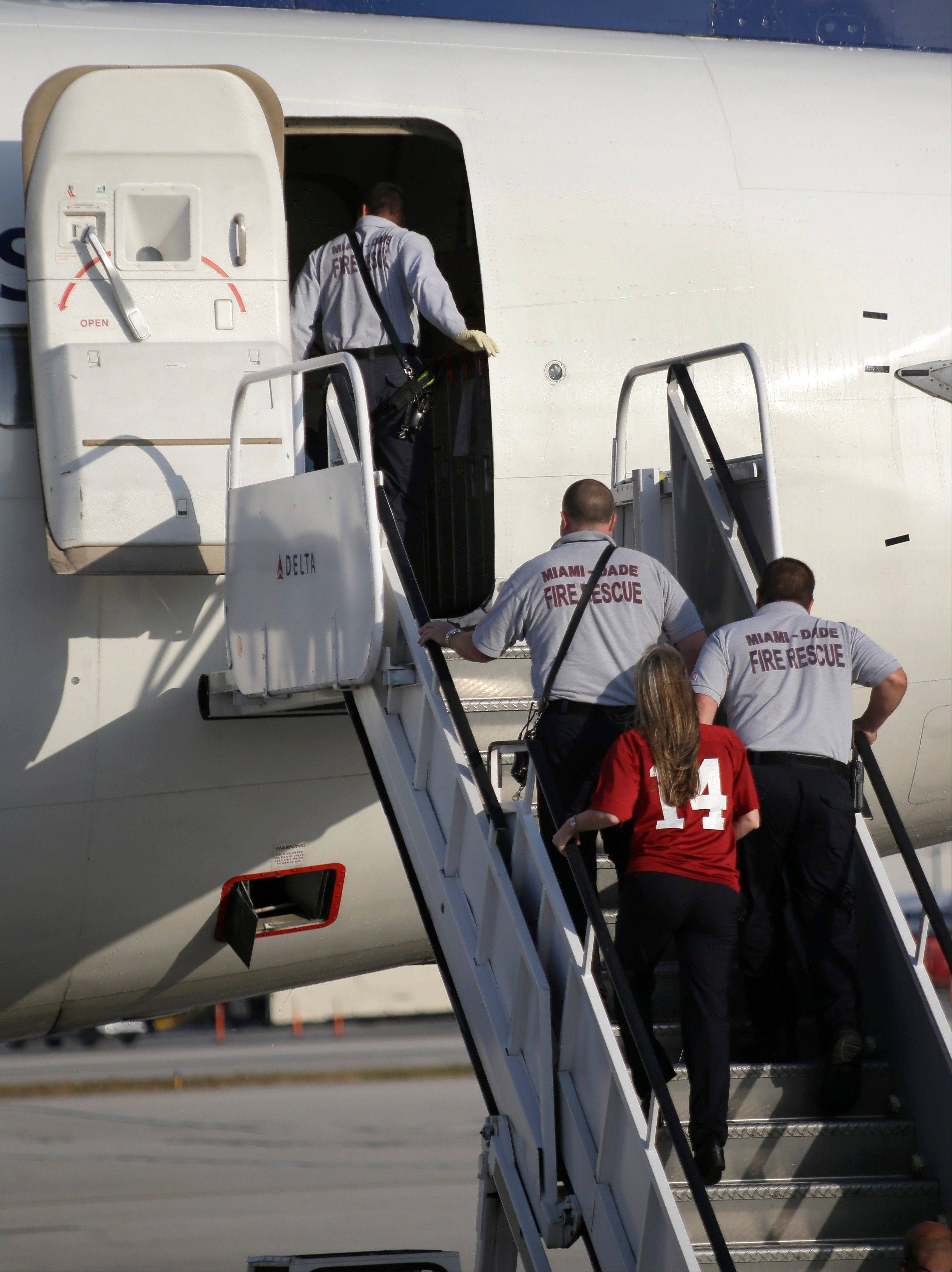 Paramedics board a plane carrying the Alabama football team Wednesday after their arrival at Miami International Airport. Reserve offensive lineman Arie Koundjio was treated for dehydration when the plane landed.