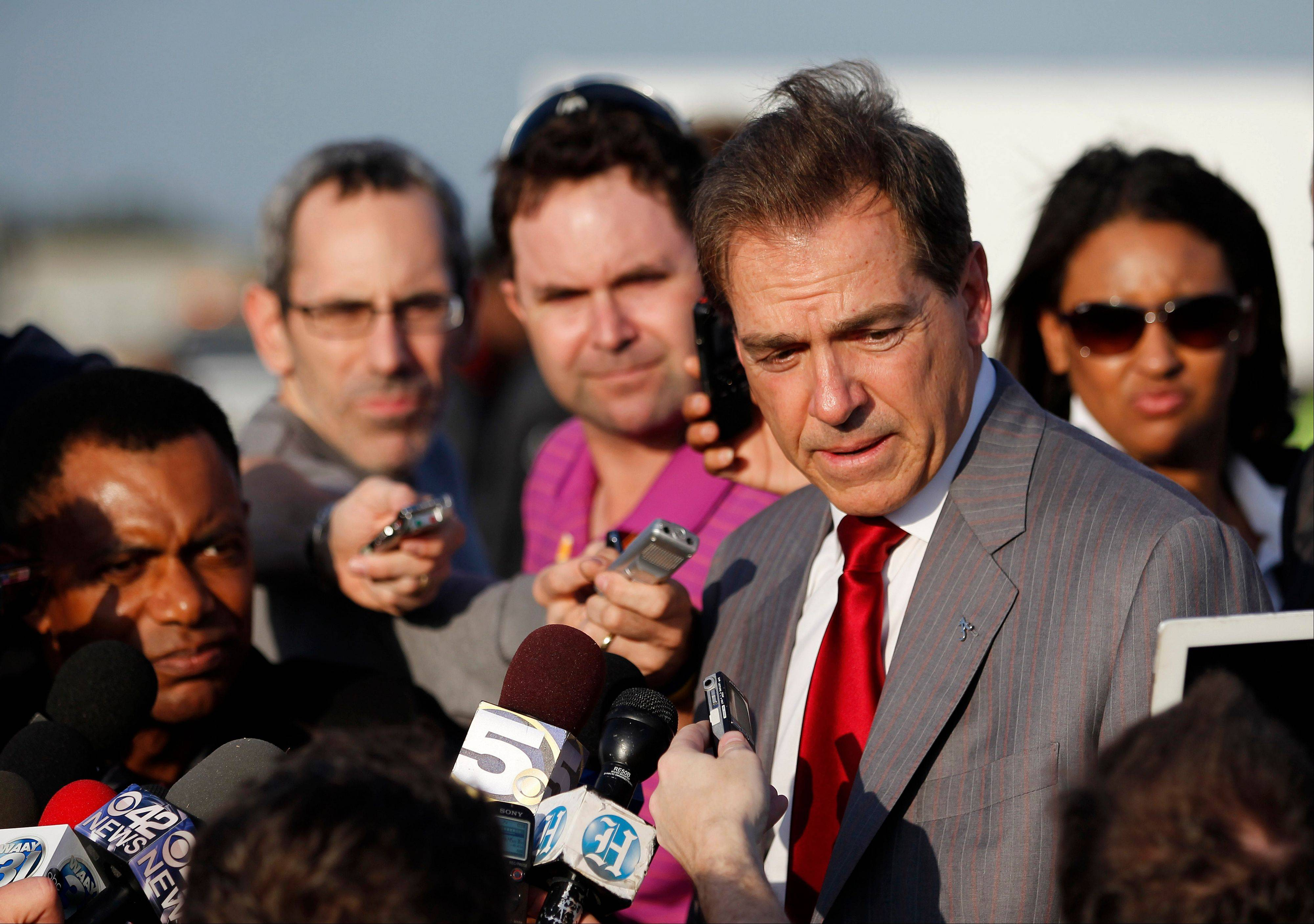Alabama head coach Nick Saban, foreground, speaks to the media Wednesday after the Crimson Tide arrived at Miami International Airport.