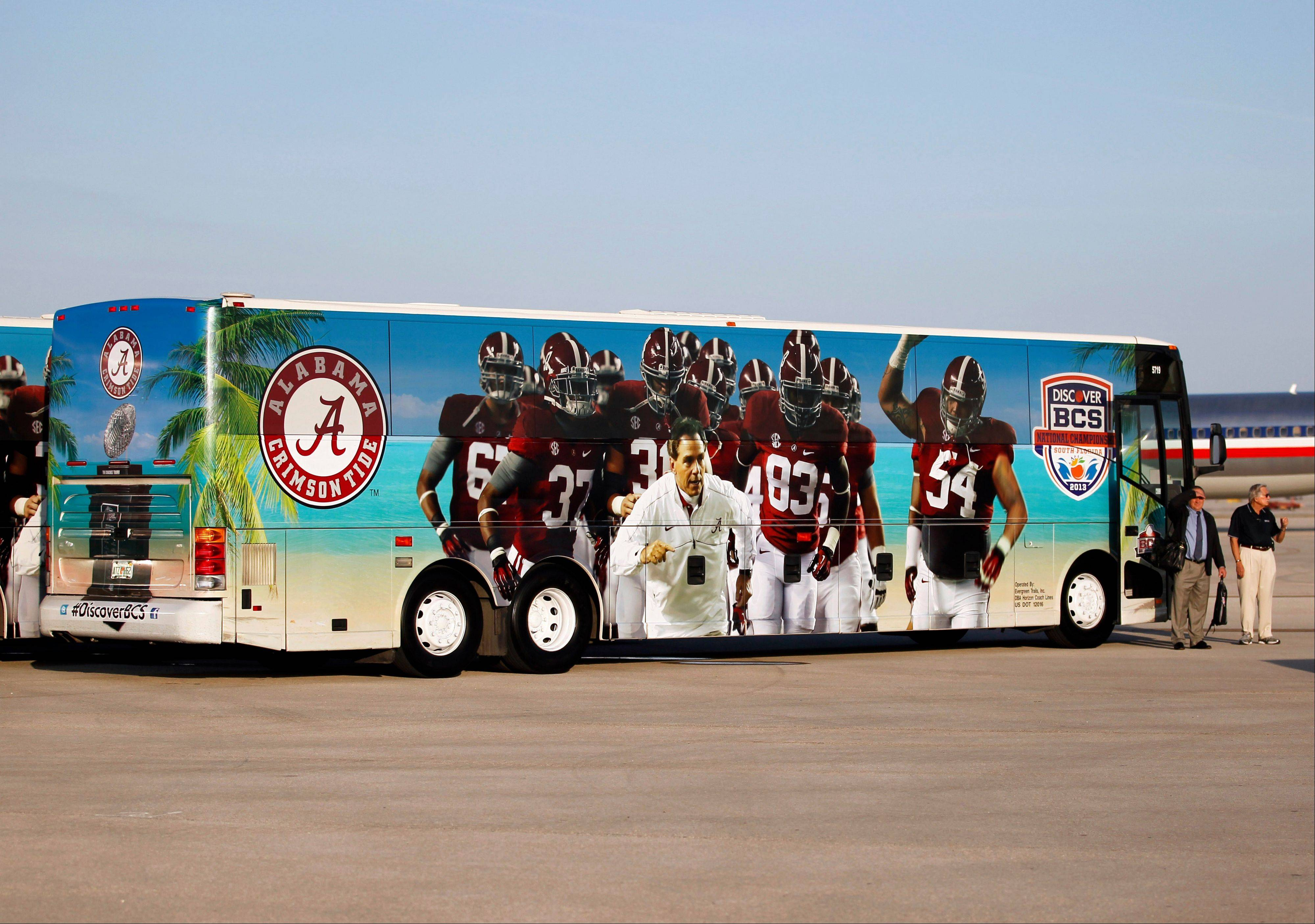 A bus with the image of head coach Nick Saban and players on the side prepares to take the team from Miami International Airport.