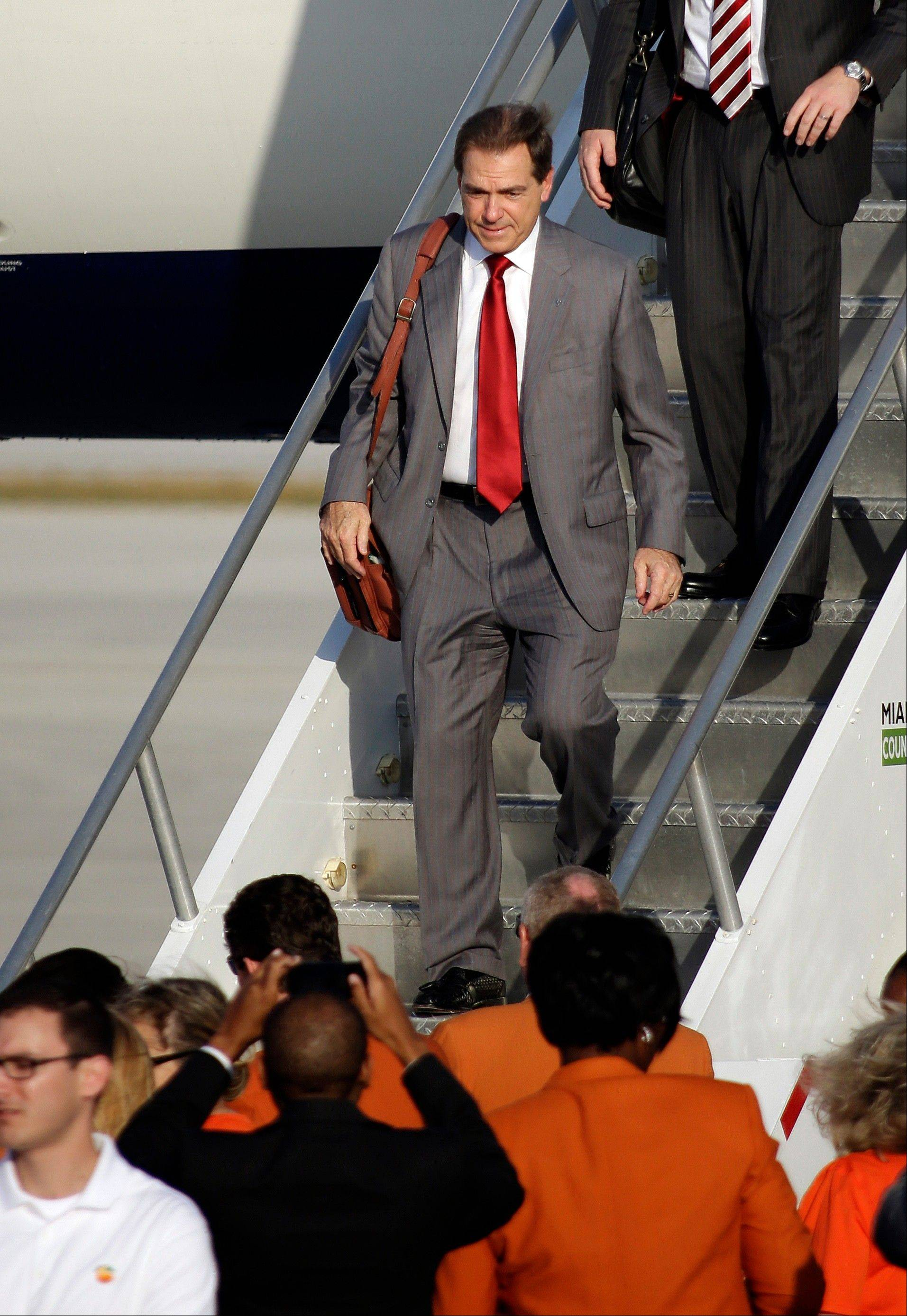 Alabama head coach Nick Saban steps off the team plane Wednesday upon arrival at Miami International Airport.