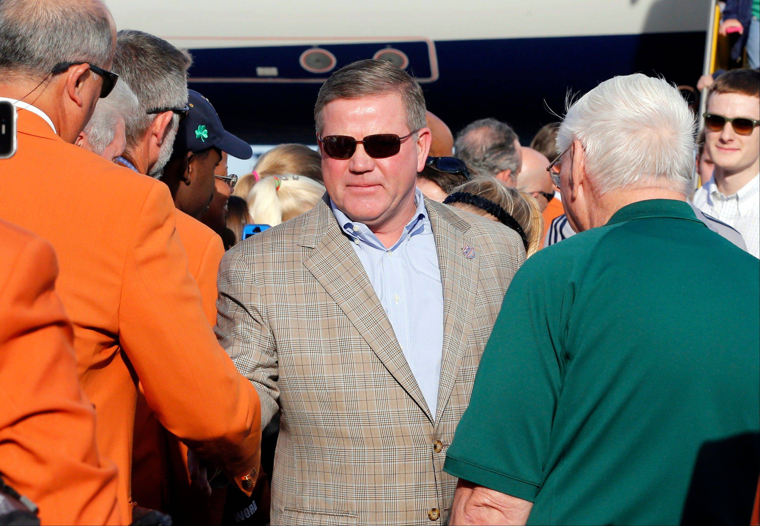 Notre Dame head coach Brian Kelly is greeted by BCS officials Wednesday as he arrives in Fort Lauderdale, Fla.