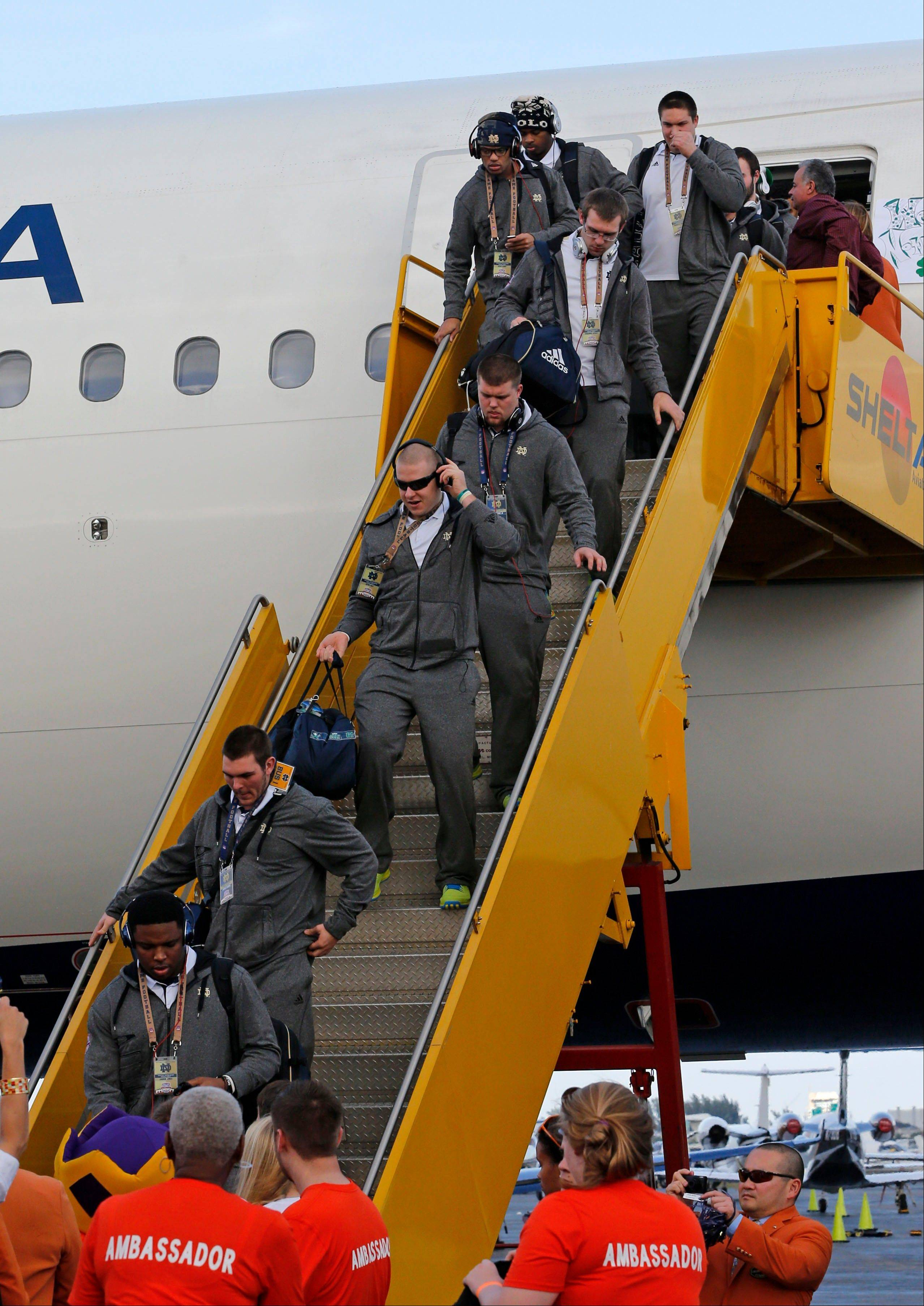 Notre Dame players deplane Wednesday after arriving in Fort Lauderdale, Fla.