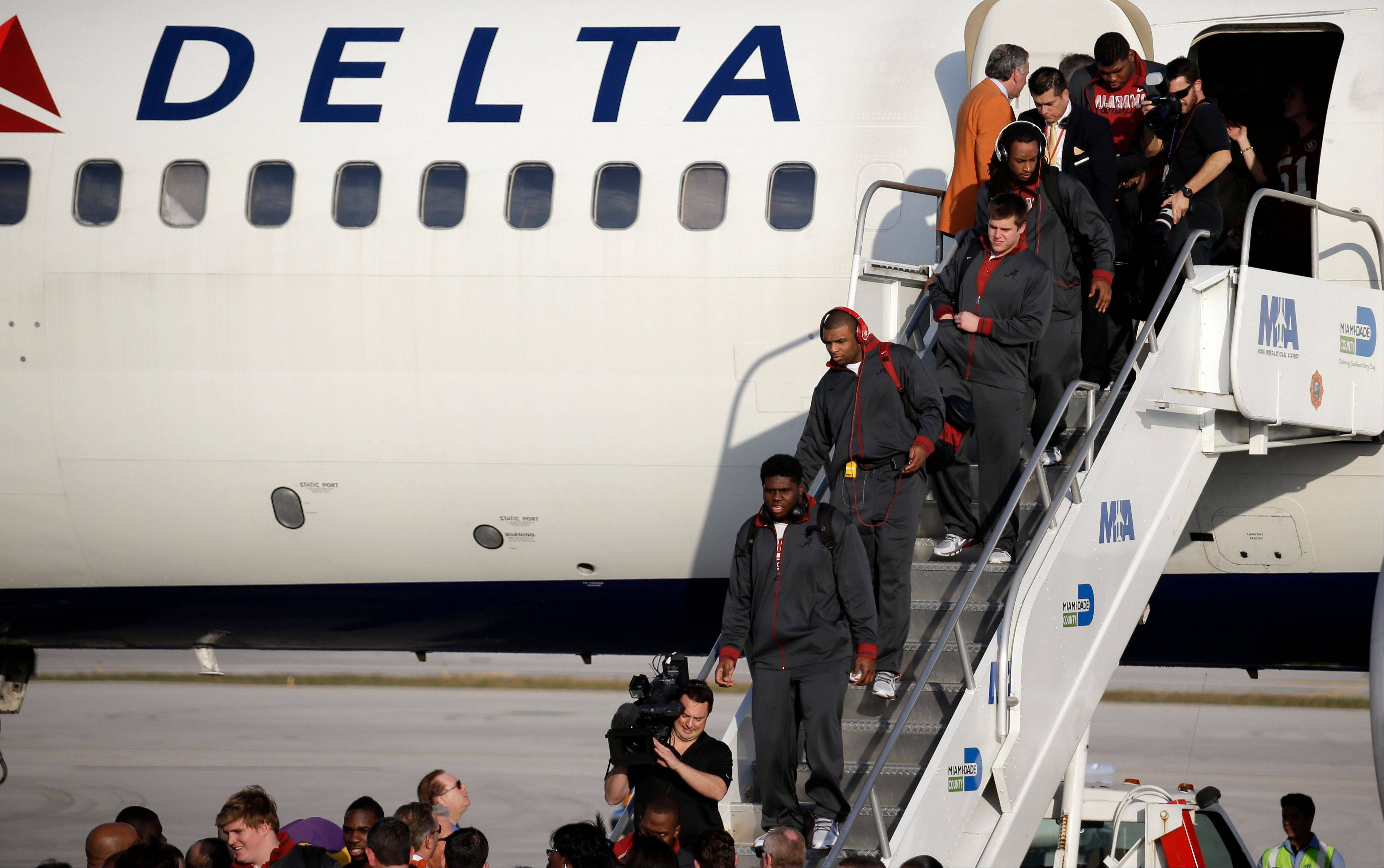 Alabama players deplane Wednesday after arriving at Miami International Airport in Miami.