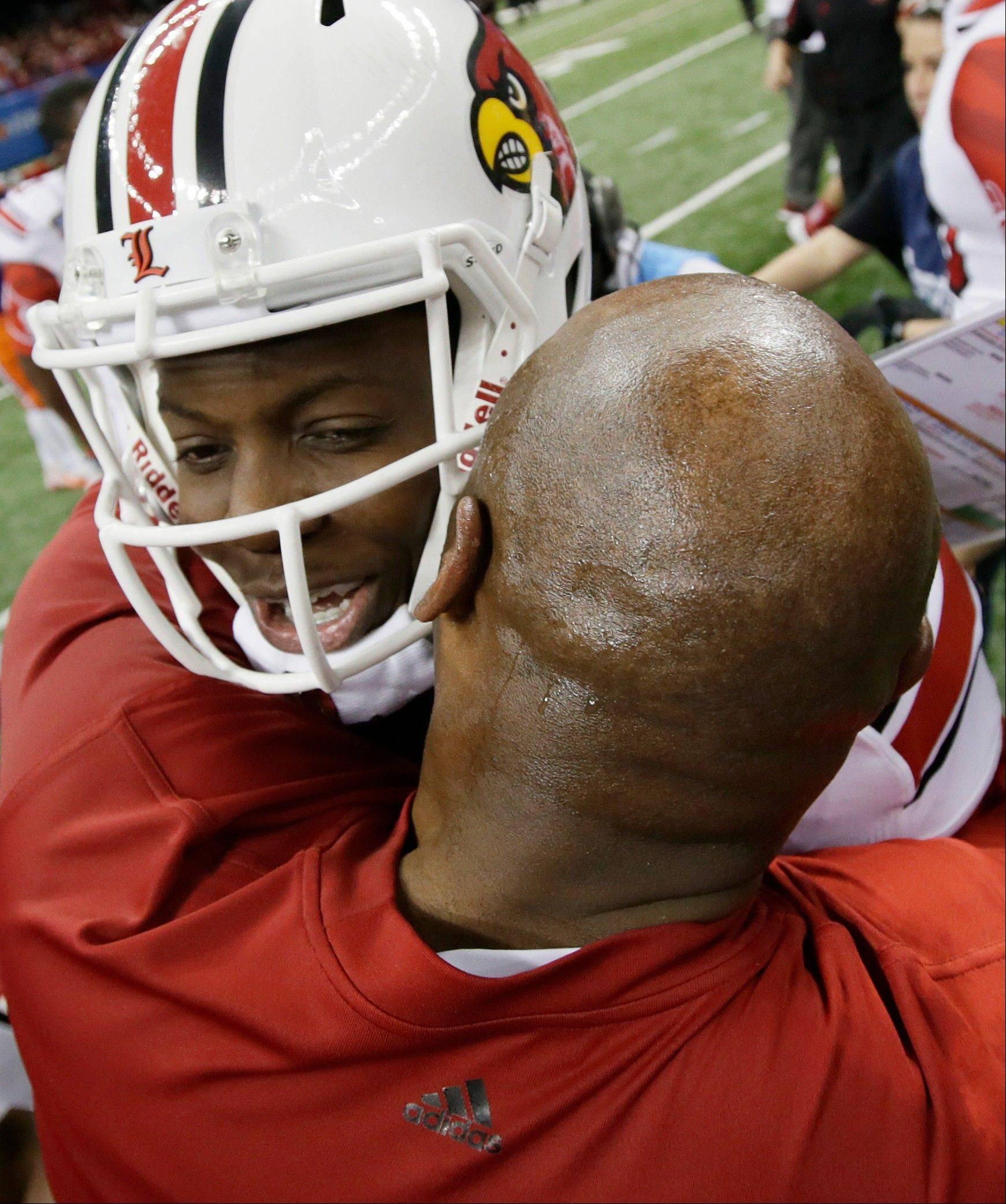 Louisville quarterback Teddy Bridgewater (5) hugs coach Charlie Strong following a 33-23 win over Florida in the Sugar Bowl Wednesday in New Orleans.