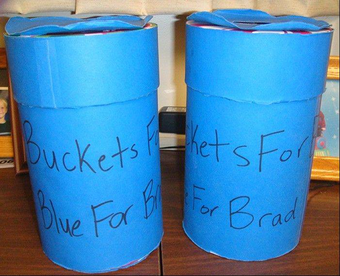 "These blue donation jars with ""Buckets for Brad"" written on them were passed around school for four days. More than $10,000 was collected for senior Brad Walls' family's medical and funeral expenses after his dad died following a fall."