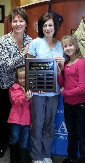 Georgana Janiec, center, receives the Caregiver of the Year Award at Visiting Angels of South Elgin from owner Arlene Petersen. Also, pictured are Janiec's children, Addison and Ava.