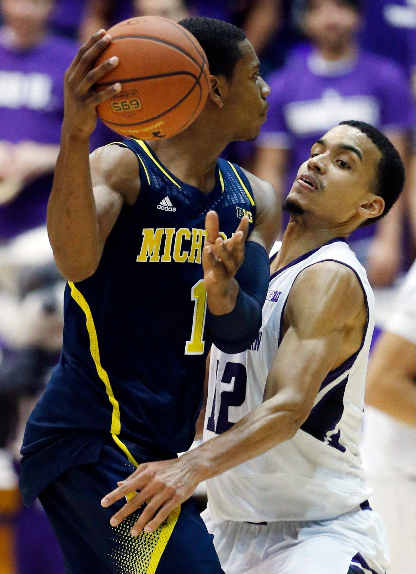 Northwestern forward Jared Swopshire, right, guards as Michigan forward Glenn Robinson III looks to pass during the second half of an NCAA college basketball game in Evanston, Ill., Thursday, Jan. 3, 2013. Michigan won 94-66. (AP Photo/Nam Y. Huh)