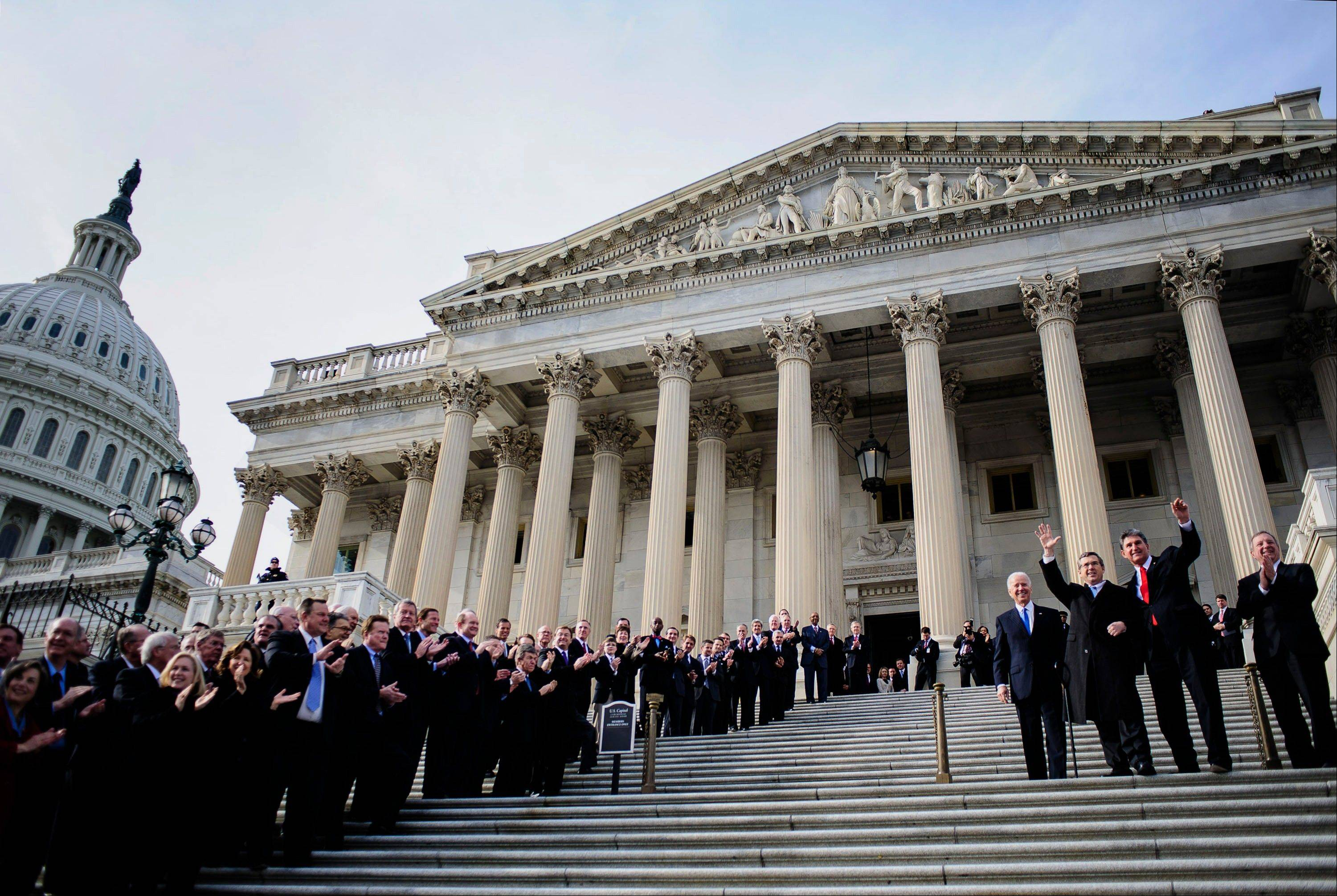 "Senator Mark Kirk, a Republican from Illinois, second left, and Senator Joe Manchin, a Democrat from West Virginia, second right, wave as U.S. Vice President Joseph ""Joe"" Biden, left, looks on while standing at the steps of the U.S. Capitol in Washington, D.C., U.S., on Thursday, Jan. 3, 2013."
