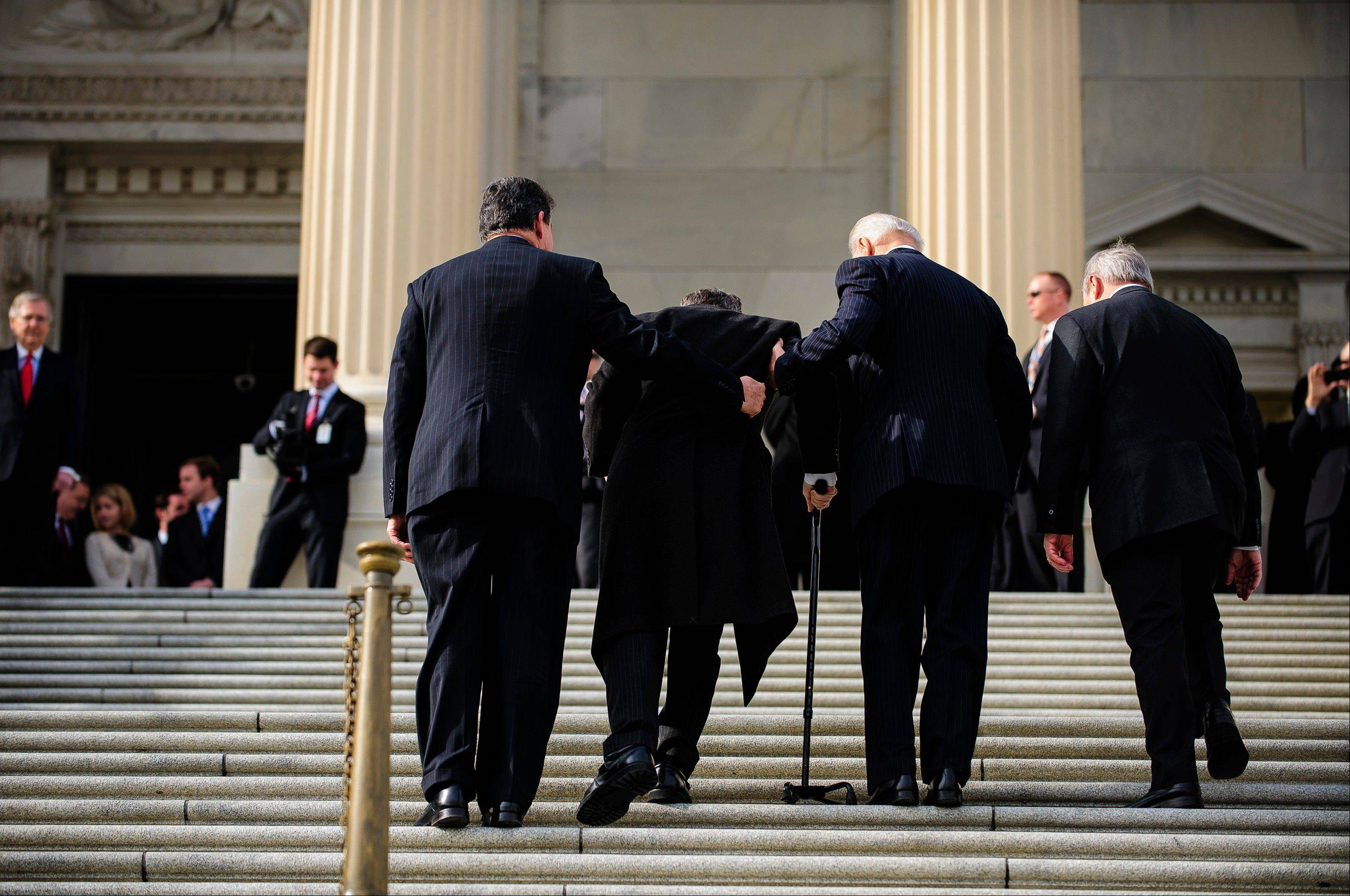 "U.S. Vice President Joseph ""Joe"" Biden, second right, and Senator Joe Manchin, a Democrat from West Virginia, left, assist Senator Mark Kirk, a Republican from Illinois, second left, up the steps of the U.S. Capitol in Washington, D.C., U.S., on Thursday, Jan. 3, 2013. Kirk returned for the first time since he suffered a stroke on Jan. 23, 2012."
