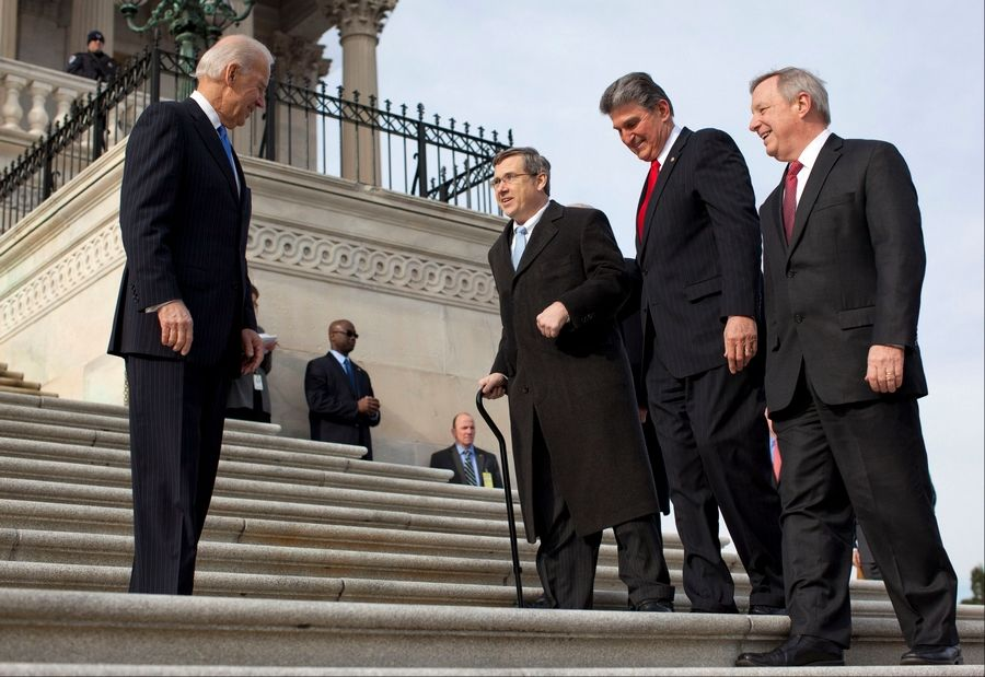 Sen. Mark Kirk, second from left, climbs the Capitol steps accompanied by Sen. Joe Manchin of West Virginia and Senate Majority whip Richard Durbin of Illinois, right. Vice President Joe Biden watches, at left. Kirk said he often visualized climbing the 45 steps as a source of inspiration during his months of physical therapy after a major stroke last year.