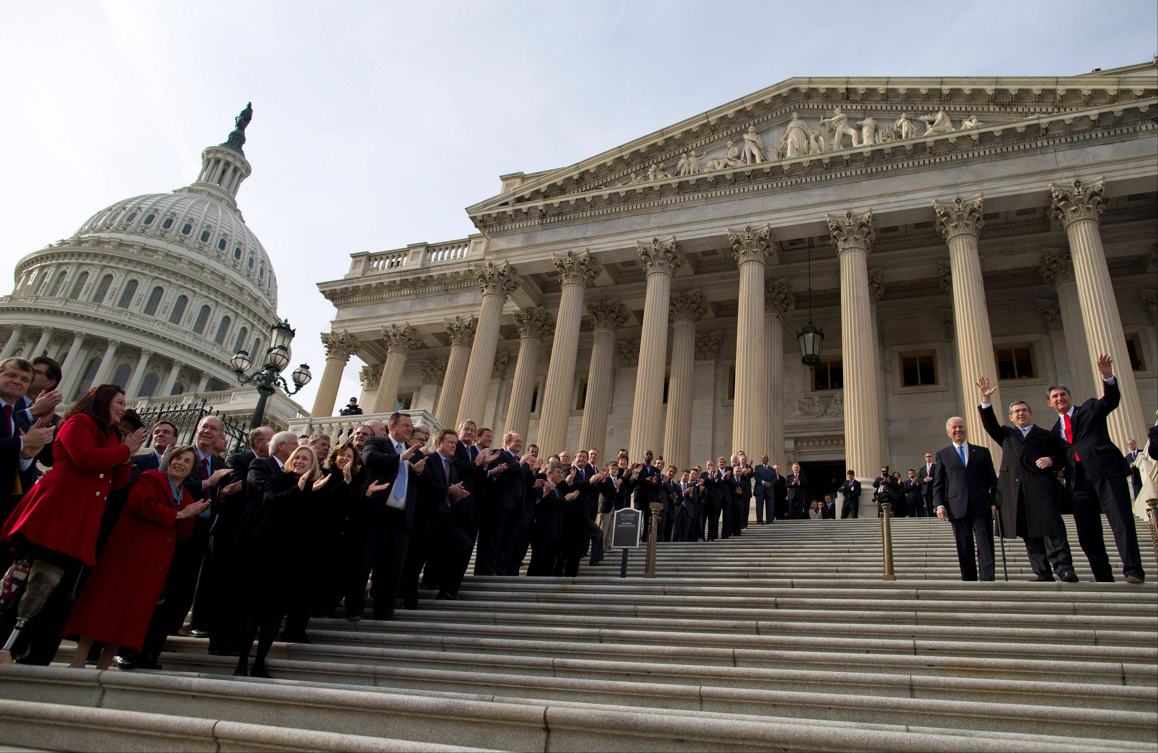 Sen. Mark Kirk, a Highland Park Republican, waves as he walks up the Capitol steps to mark his return to Congress. Members of Congress line the steps and Kirk is accompanied by Sen. Joe Manchin of West Virginia, to his right, and Vice President Joe Biden, on his left.