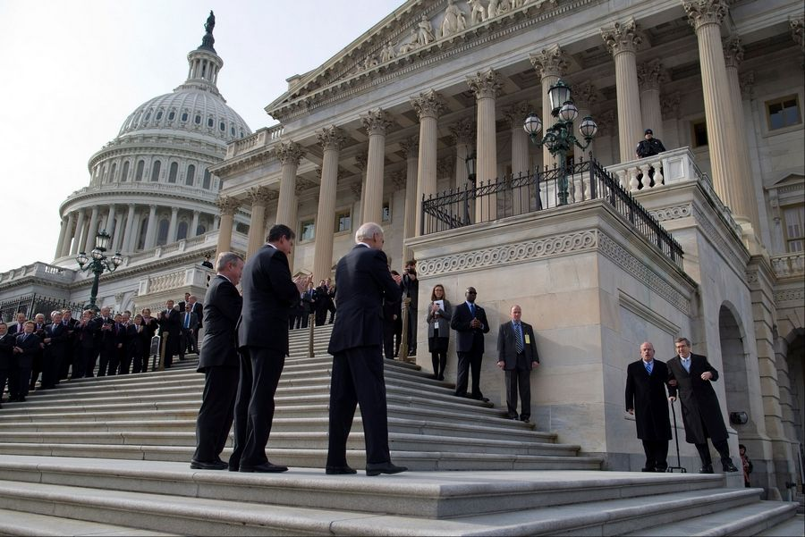 U.S. Sen. Mark Kirk, right, helped by Senate Sergeant at Arms and Doorkeeper Terrance Gainer, walks on Capitol Hill in Washington, D.C., before climbing the steps to the Senate. Applauding in the foreground, from left, are Senate Majority Whip Richard Durbin of Illinois, Sen. Joe Manchin of West Virginia and Vice President Joe Biden.