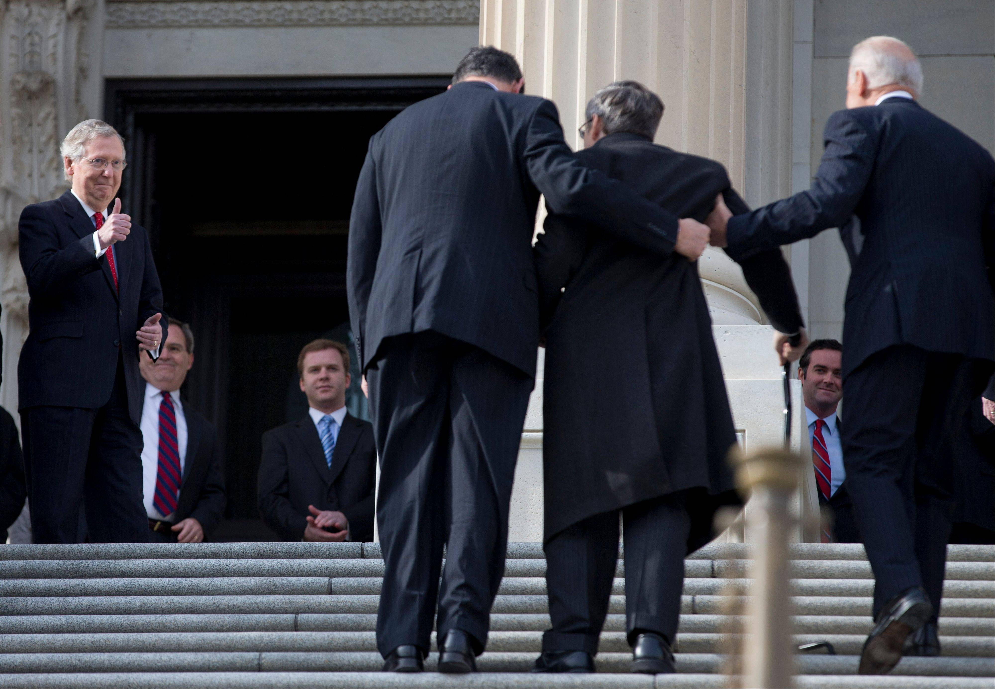 Senate Minority Leader Sen. Mitch McConnell of Kentucky gives a thumbs-up as Sen. Mark Kirk, of Highland Park, second from right, walks up the steps to the Senate door of the Capitol building. Kirk is accompanied by Vice President Joe Biden, right, and Sen. Joe Manchin.