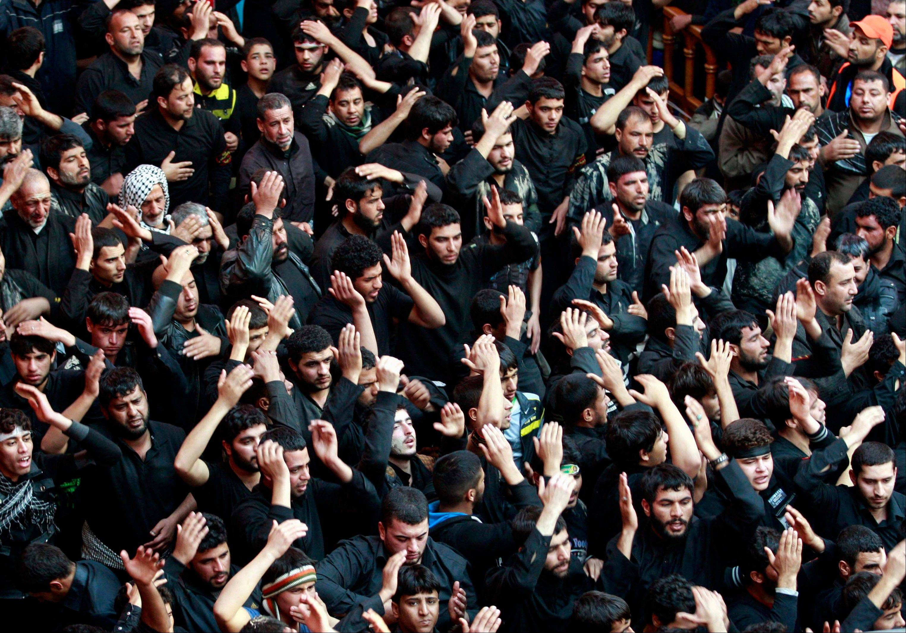 Shiite Muslim worshippers beat themselves inside the holy shrine of Imam Hussein to mark the Muslim festival of Arbaeen in Karbala, 50 miles south of Baghdad. Iraqi officials say a car bomb has struck a procession of Shiite pilgrims south of Baghdad, killing at least 12 and wounding dozens.