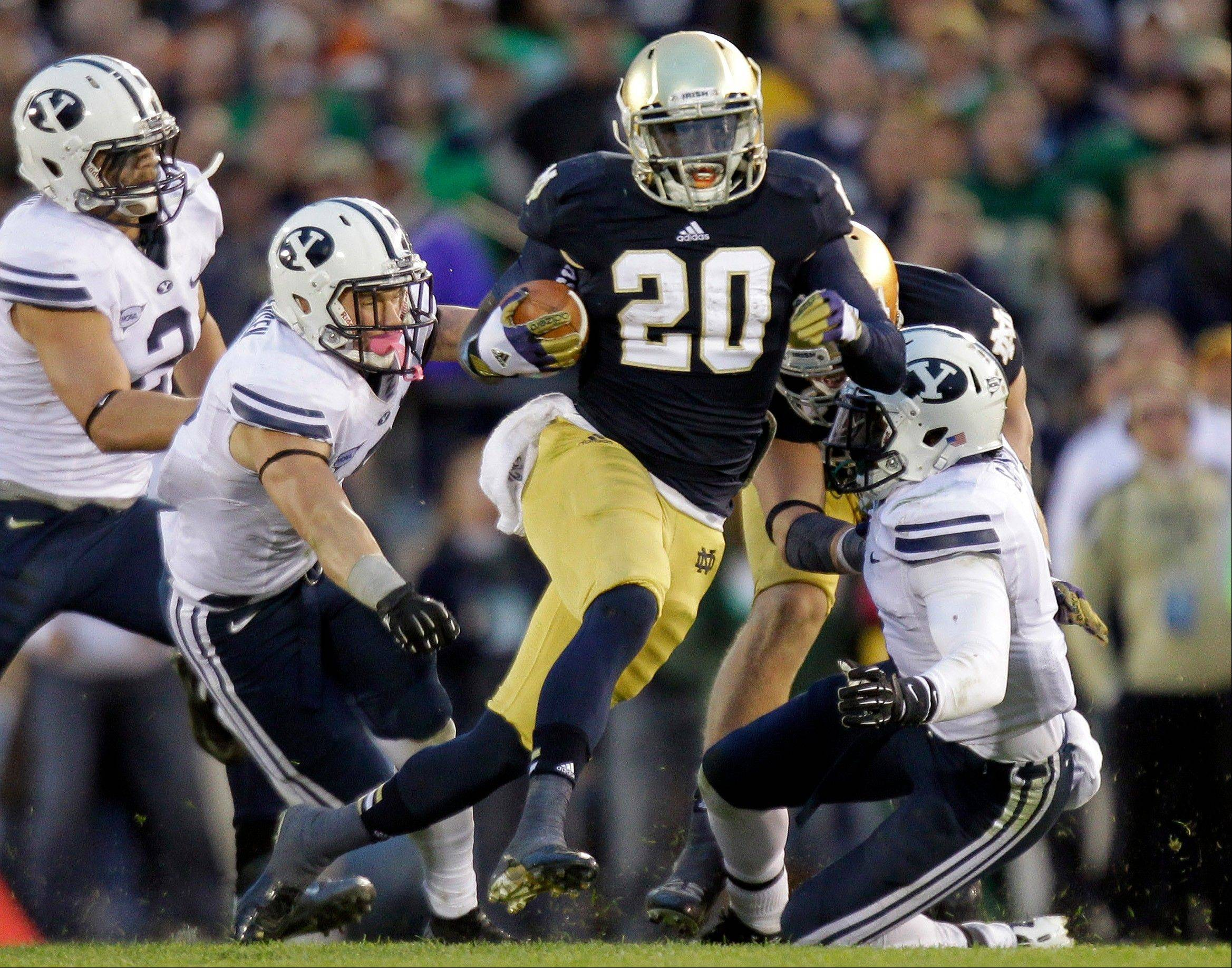 Notre Dame running back Cierre Wood, center, cuts between Brigham Young defenders Spencer Hadley, left, Daniel Sorensen, left center, and Joe Sampson. With the national championship on the line, two throwback offenses will slug it out. No. 1 Notre Dame and No. 2 Alabama rely heavily on the run, and that doesn't figure to change in the biggest game of the year.