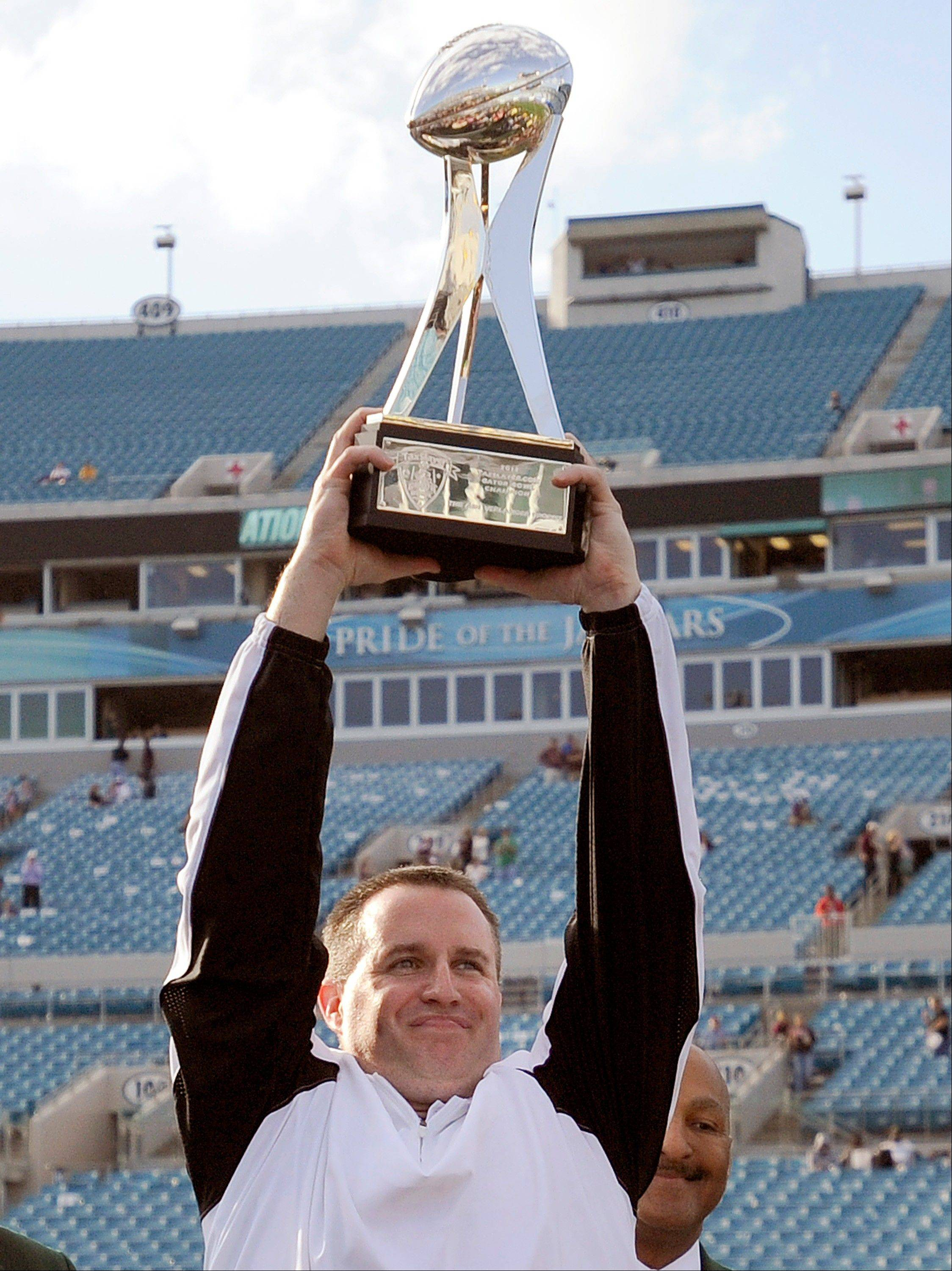 Northwestern head coach Pat Fitzgerald celebrates with the trophy after their 34-20 win over Mississippi State in the Gator Bowl on Tuesday.