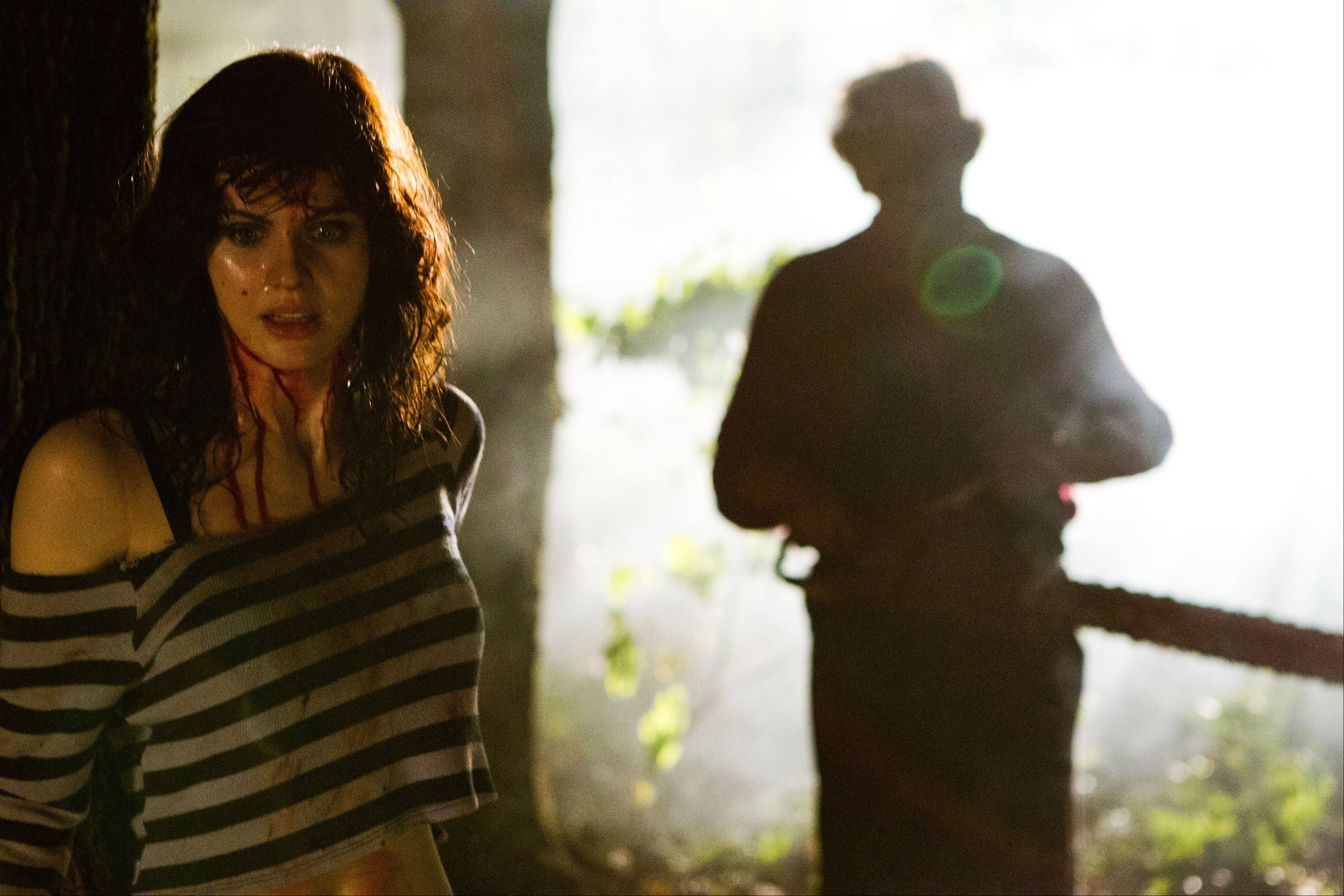 "Heather Miller (Alexandra Daddario) is unaware Leatherface (Dan Yeager) is closing in behind her in ""Texas Chainsaw 3-D."""