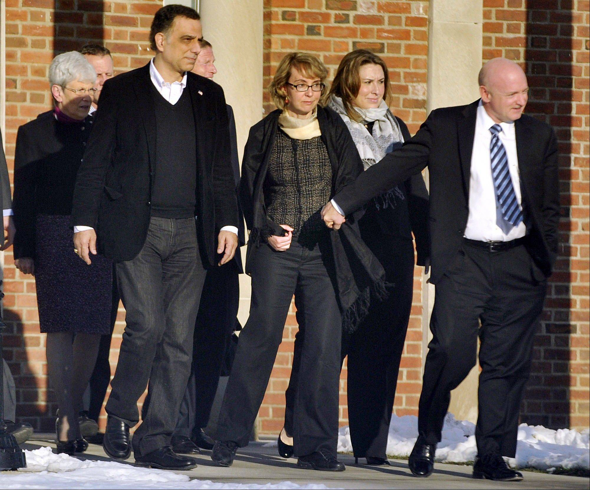 Former U.S. Rep. Gabrielle Giffords, center, holds hands Friday with her husband, Mark Kelly, while exiting Town Hall at Fairfield Hills Campus in Newtown, Conn. after meeting with Newtown First Selectman Pat Llodra and other officials.