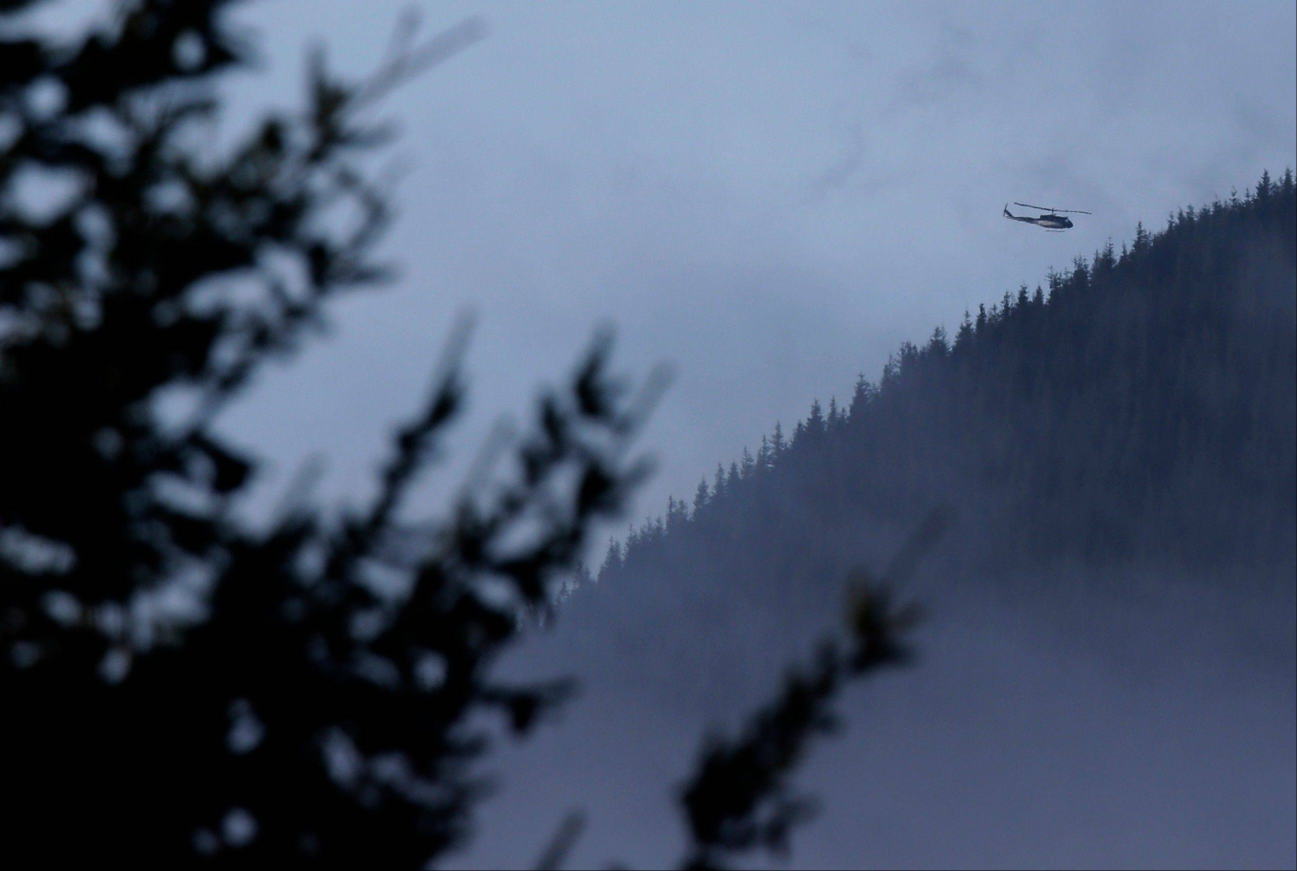 A King County Sheriff's Dept. helicopter flies Friday over rugged terrain near Mount Si in North Bend, Wash.