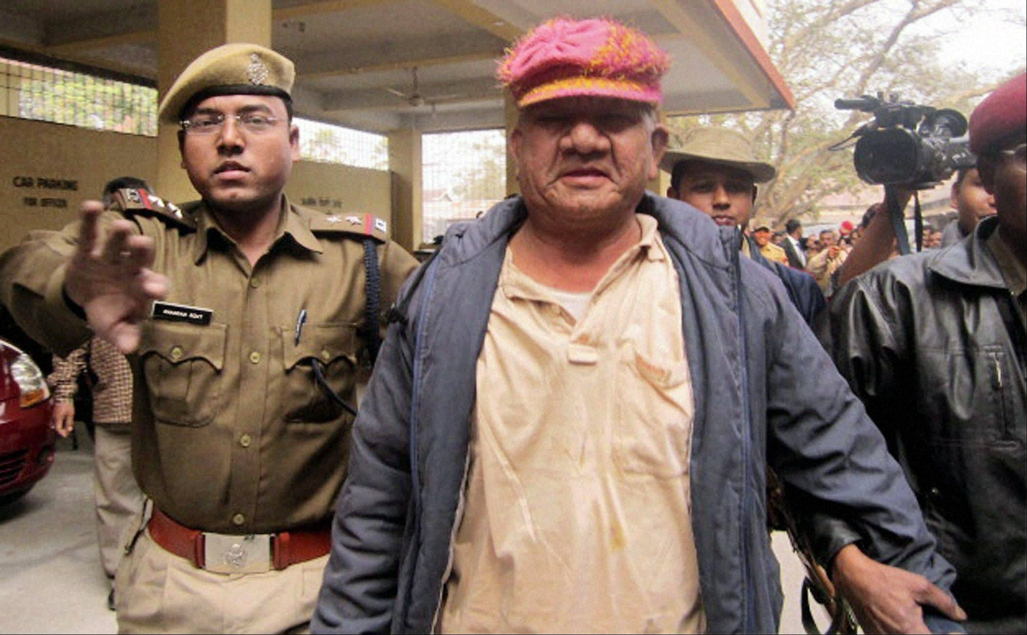 A leader of the ruling Congress party Bikram Singh Brahma, center, is escorted to a court Friday after allegations leading to his arrest on accusations he raped a woman. Footage on Indian television showed the extraordinary scene of local women surrounding Brahma, ripping off his shirt and repeatedly slapping him across the face.