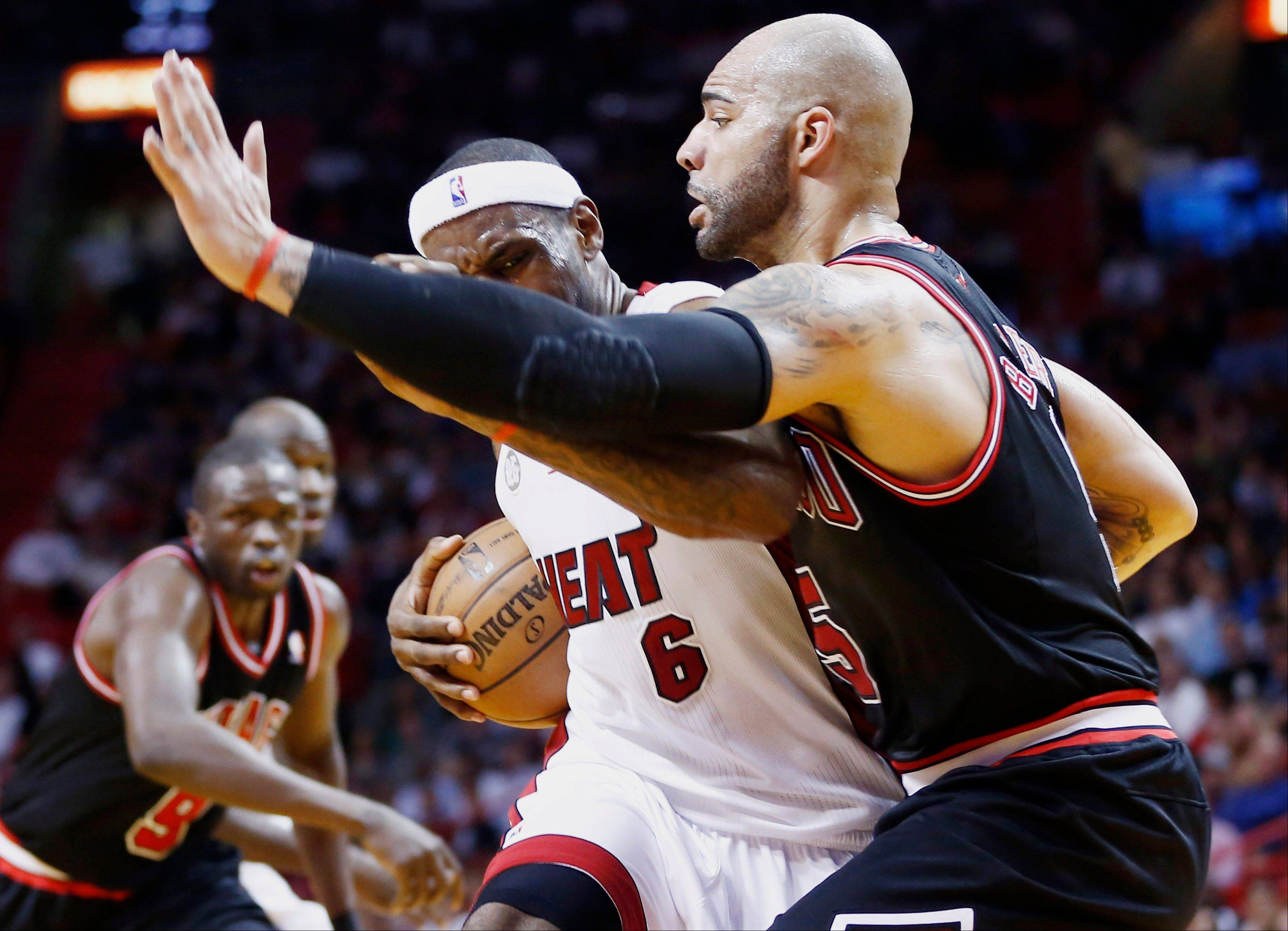 Carlos Boozer scored 27 points and the Bulls dominated on the boards to become only the third visiting team to win in Miami this season, beating the Heat 96-89 Friday night.