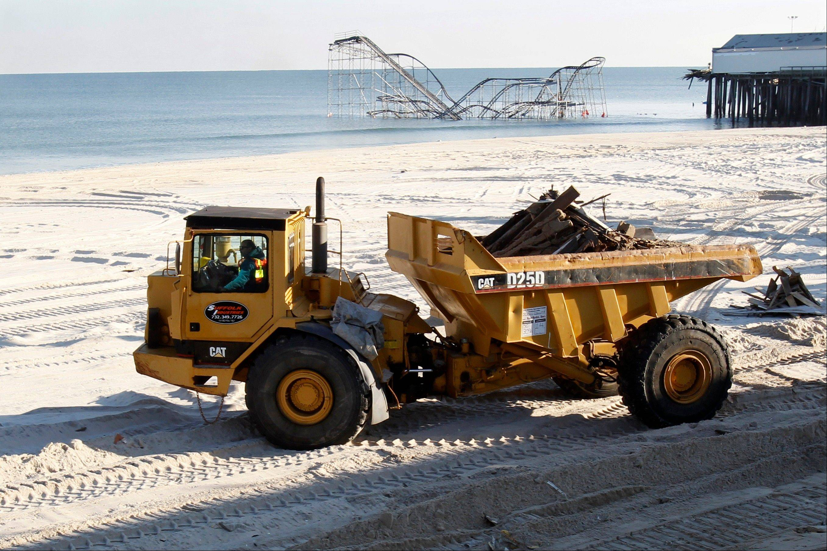 A large construction vehicle carries remnants of the boardwalk Thursday in Seaside Heights, N.J., that was destroyed two months ago by Superstorm Sandy. Under intense pressure from angry Republicans, House Speaker John Boehner has agreed to a vote this week on aid for Superstorm Sandy recovery.
