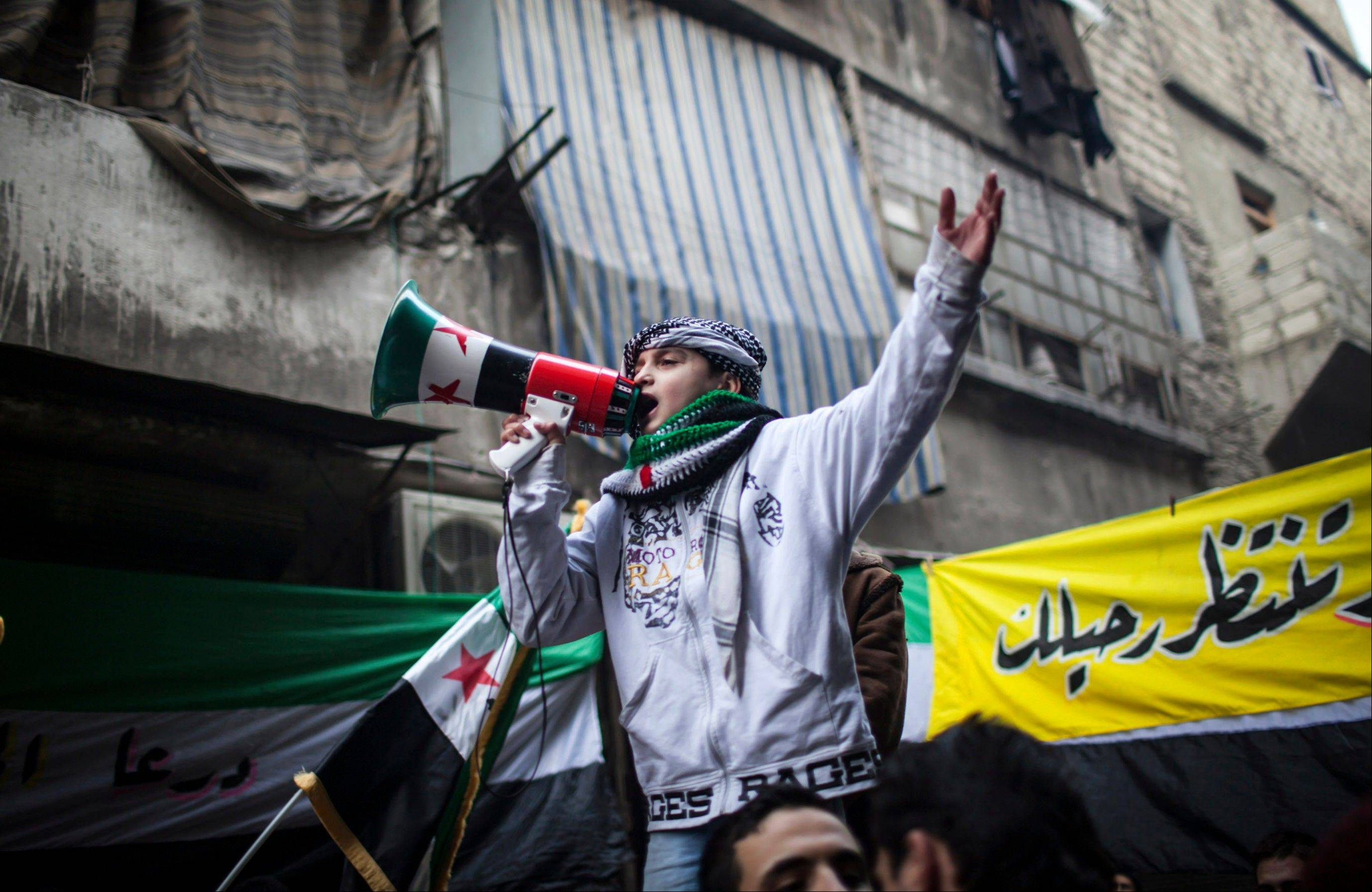 A child uses a megaphone Friday to lead others in chanting Free Syrian Army slogans during a demonstration in the neighborhood of Bustan Al-Qasr, Aleppo, Syria.