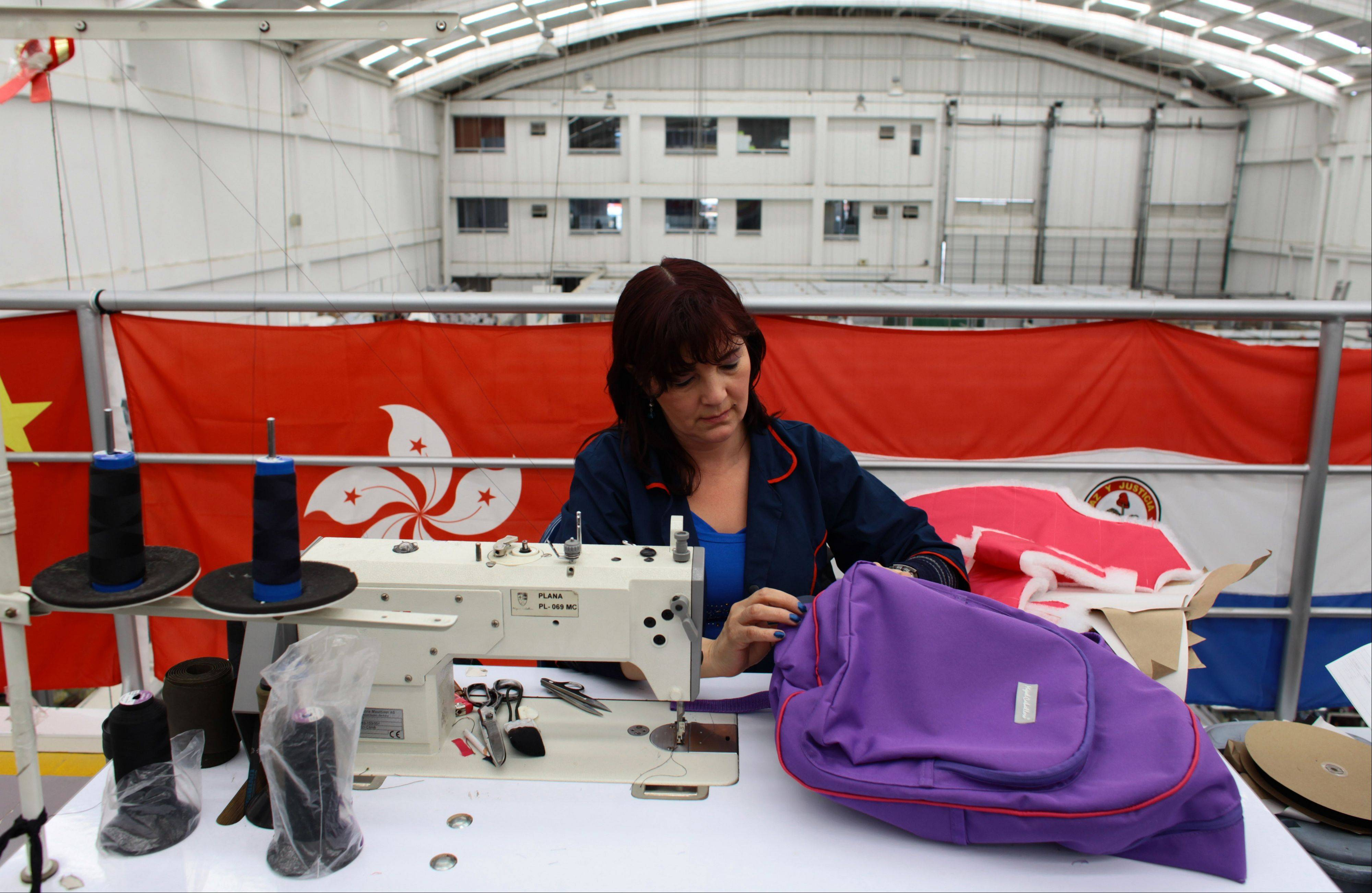 A seamstress works Thursday on an armored backpack designed for a child at the Miguel Caballero factory on the outskirts of Bogota, Colombia.