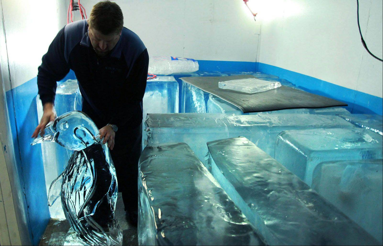 Dan Rebholz of Wheaton stores 300-pound blocks of ice he froze for carving and his finished pieces inside a walk-in freezer at his Villa Park studio.