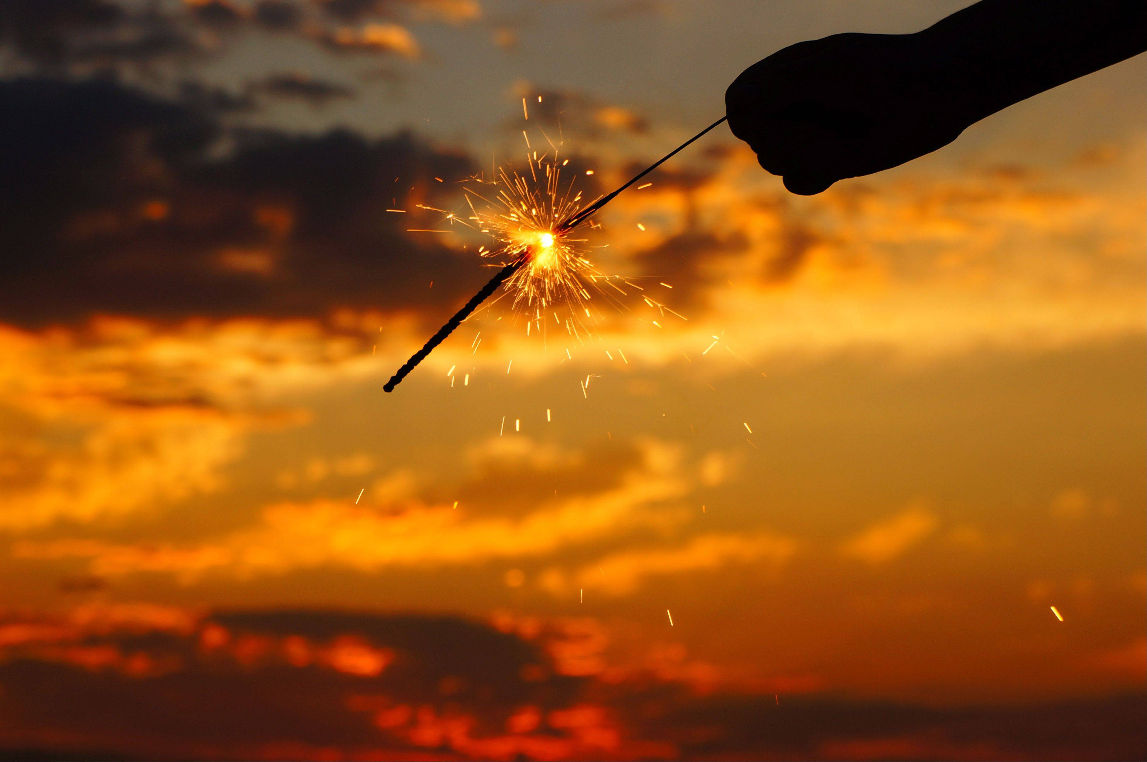 A child holds a sparkler on the Fourth of July as the sun sets over Buckatabon Lake in Conover, Wisconsin.