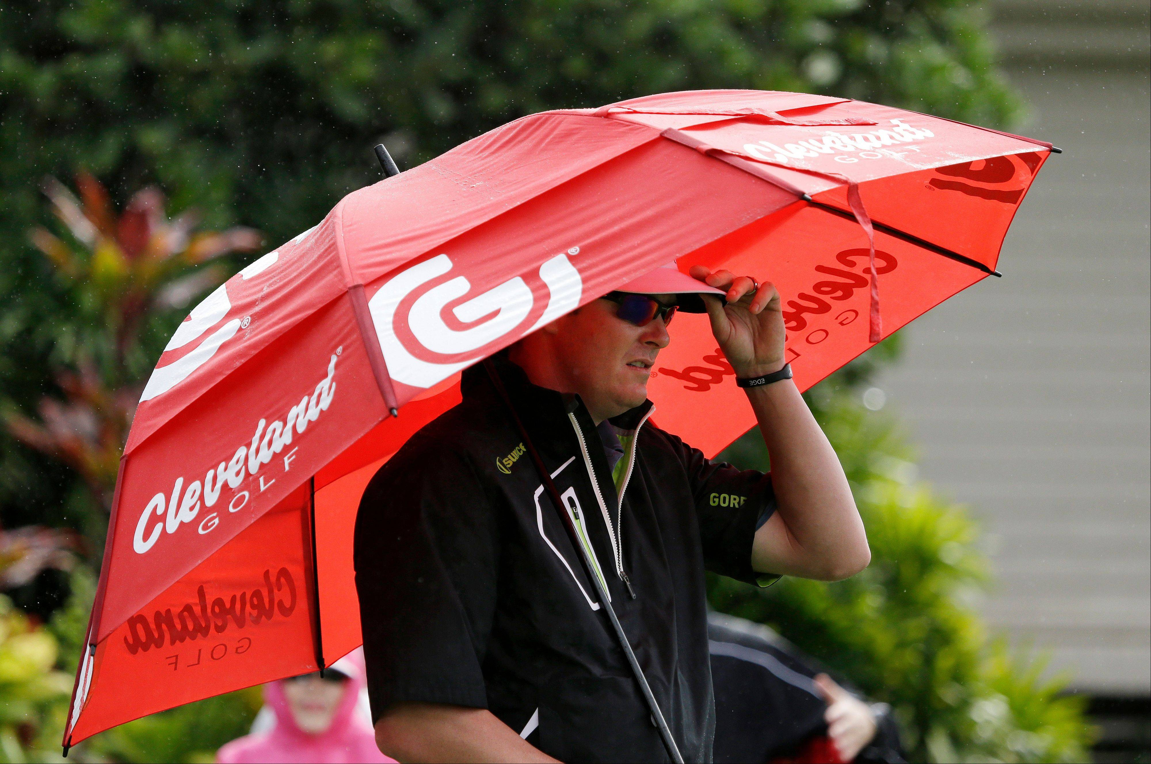 Charlie Beljan holds an umbrella as he waits his turn to tee off in the first round at the Tournament of Champions golf tournament on Friday, Jan. 4, 2013, in Kapalua, Hawaii.