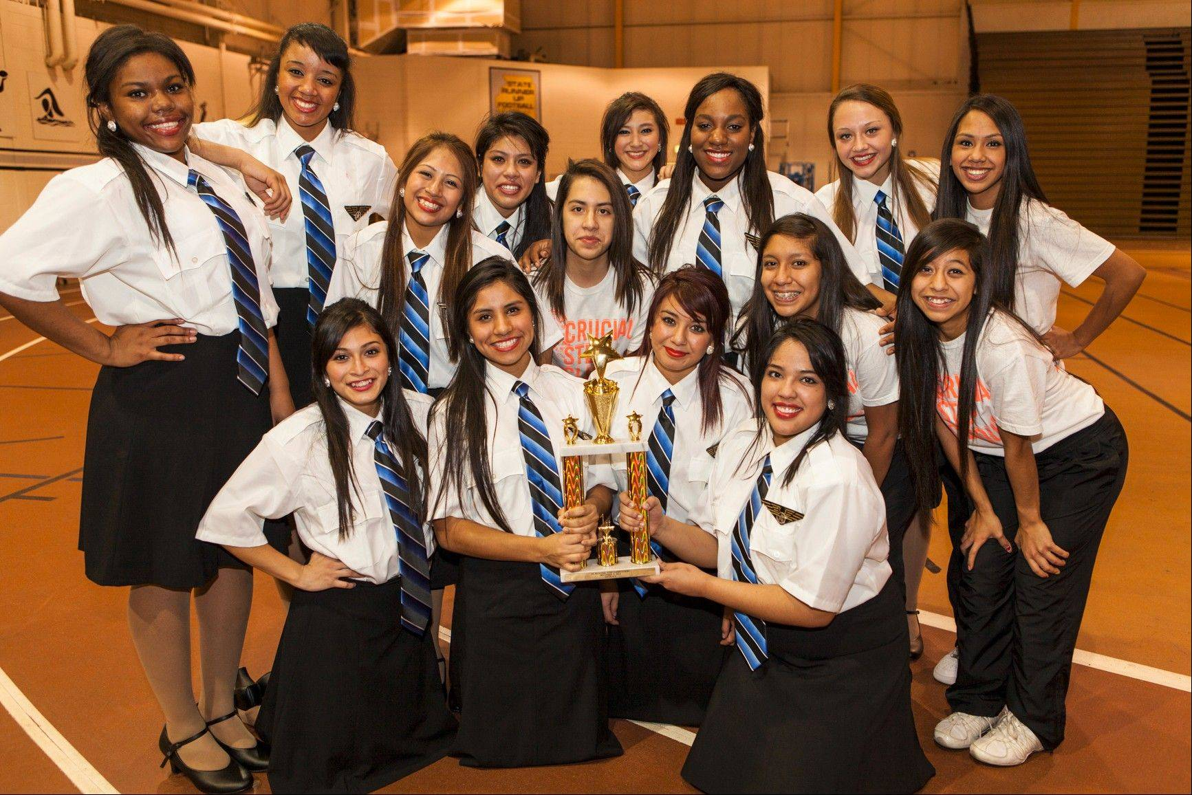 The Wheeling Crucial Step Clique displays its first place trophy at the Illinois Step League competition. Senior Jenny Hernandez, bottom right, is wearing Rising Star wings on her shirt.