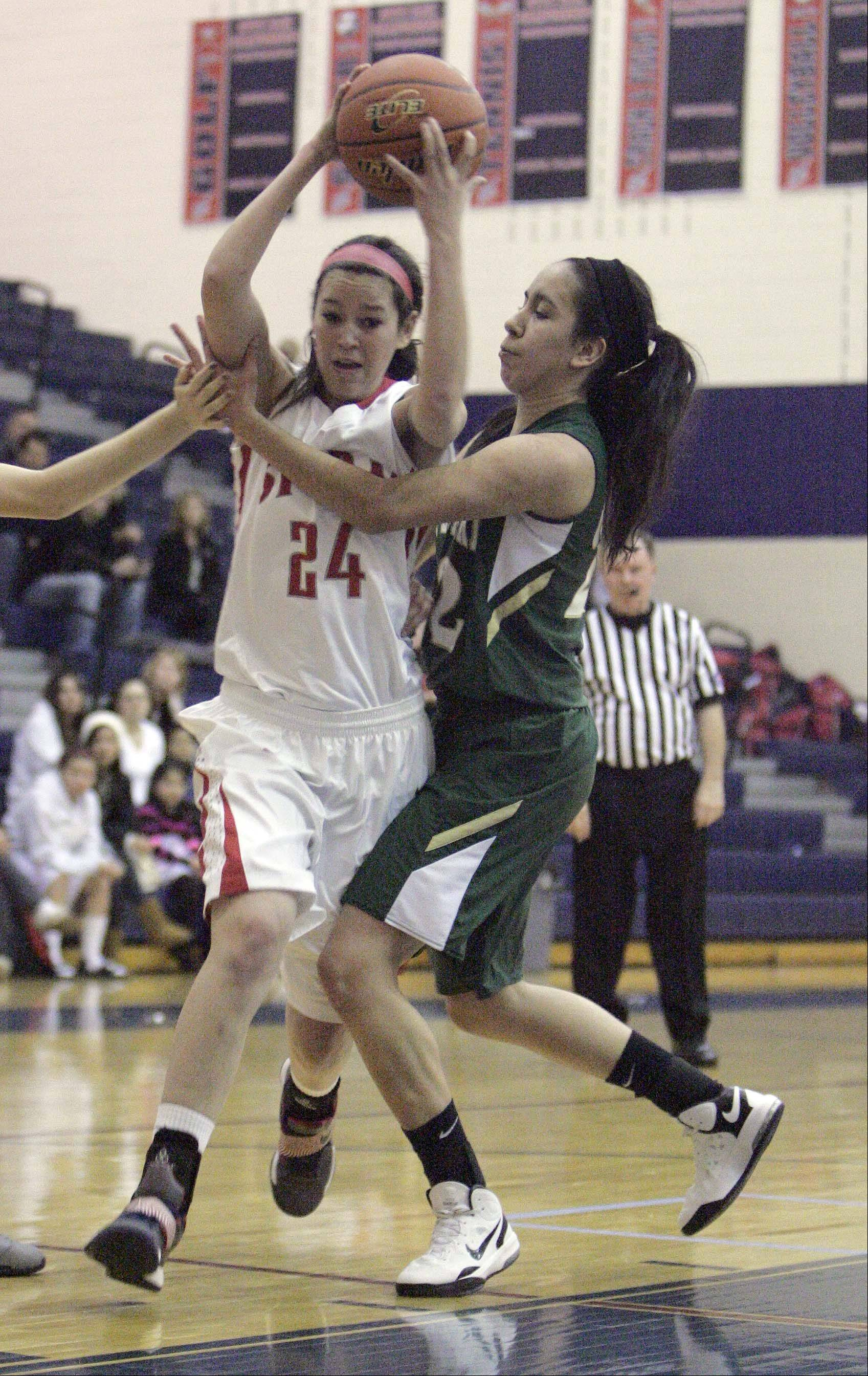 South Elgin�s Kennede Miller (24) goes to the hoop as St. Edward�s Clarissa Ramos defends Saturday at South Elgin.