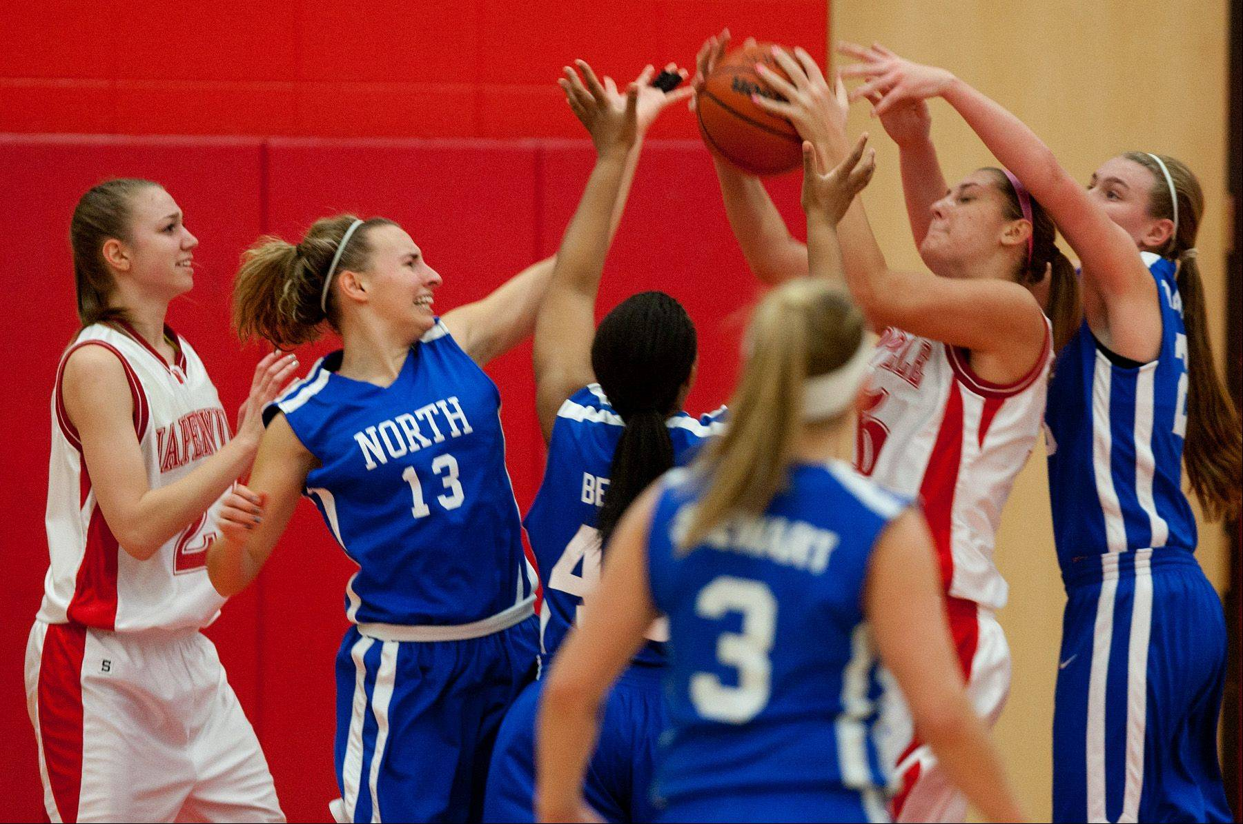 Naperville Central�s Victoria Trowbridge grabs a defensive rebound over Wheaton North, during girls basketball action in Naperville.