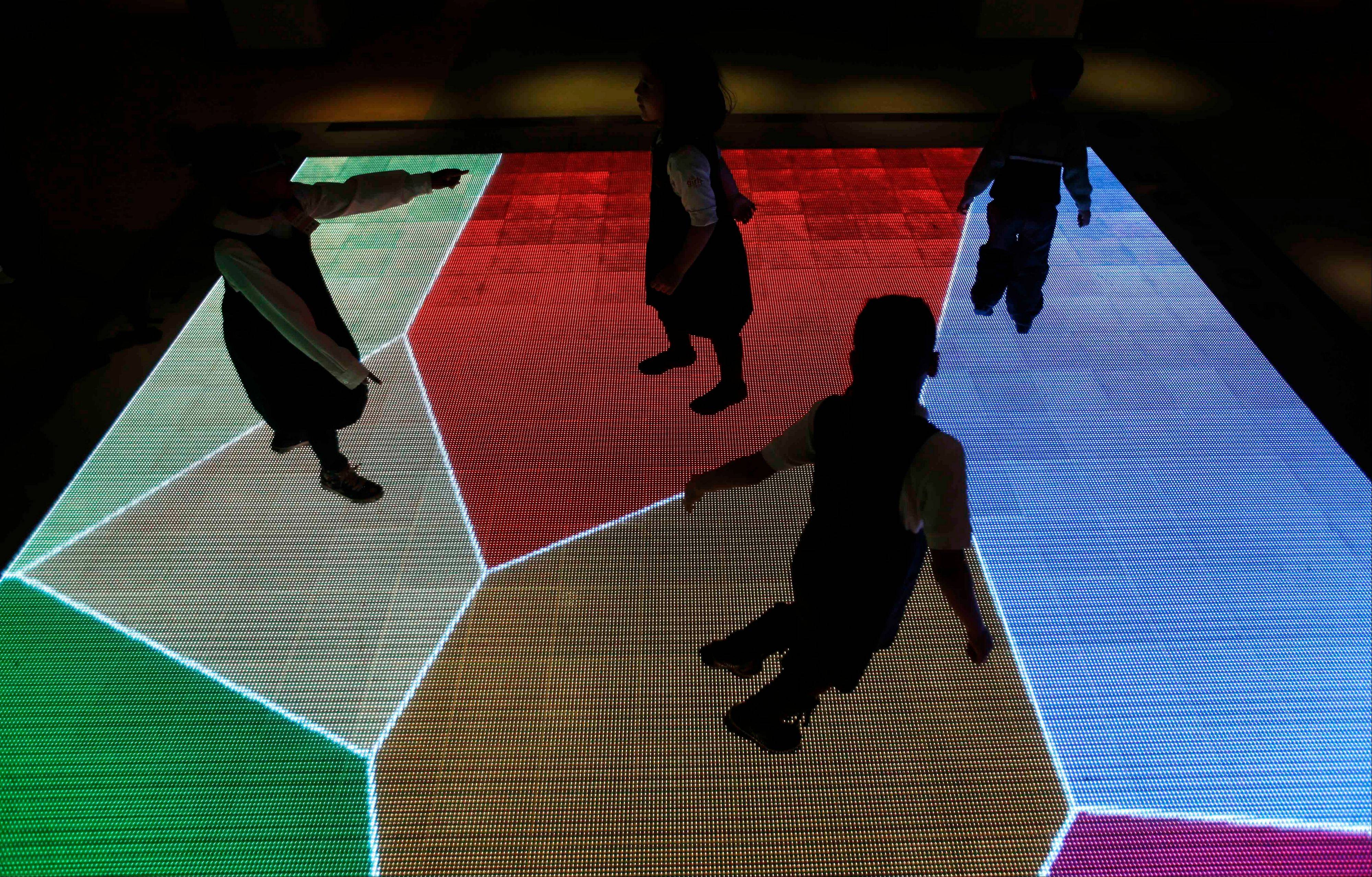 Children run across an interactive exhibit at the new National Museum of Mathematics in New York.