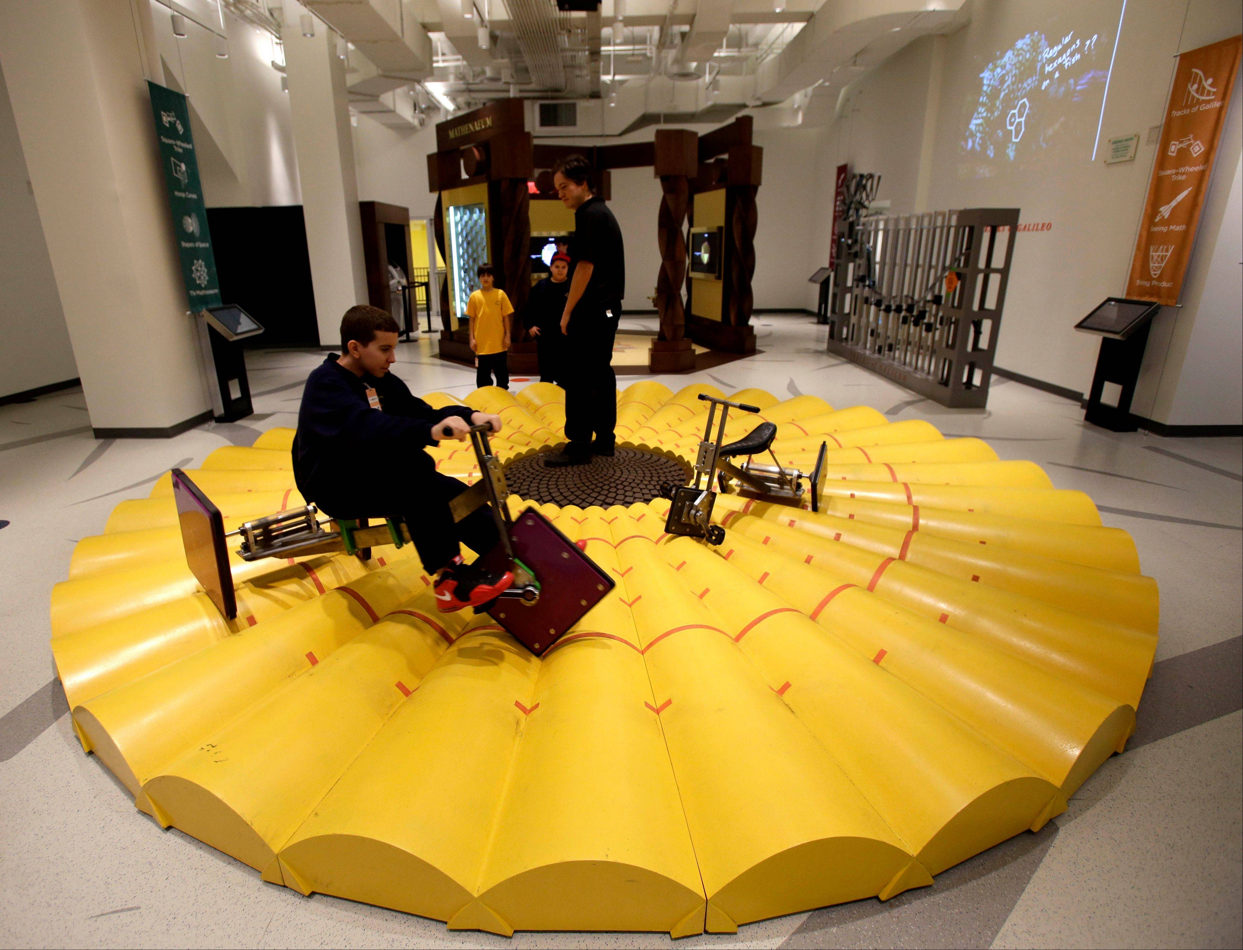 A visitor to the National Museum of Mathematics rides a tricycle with square wheels.