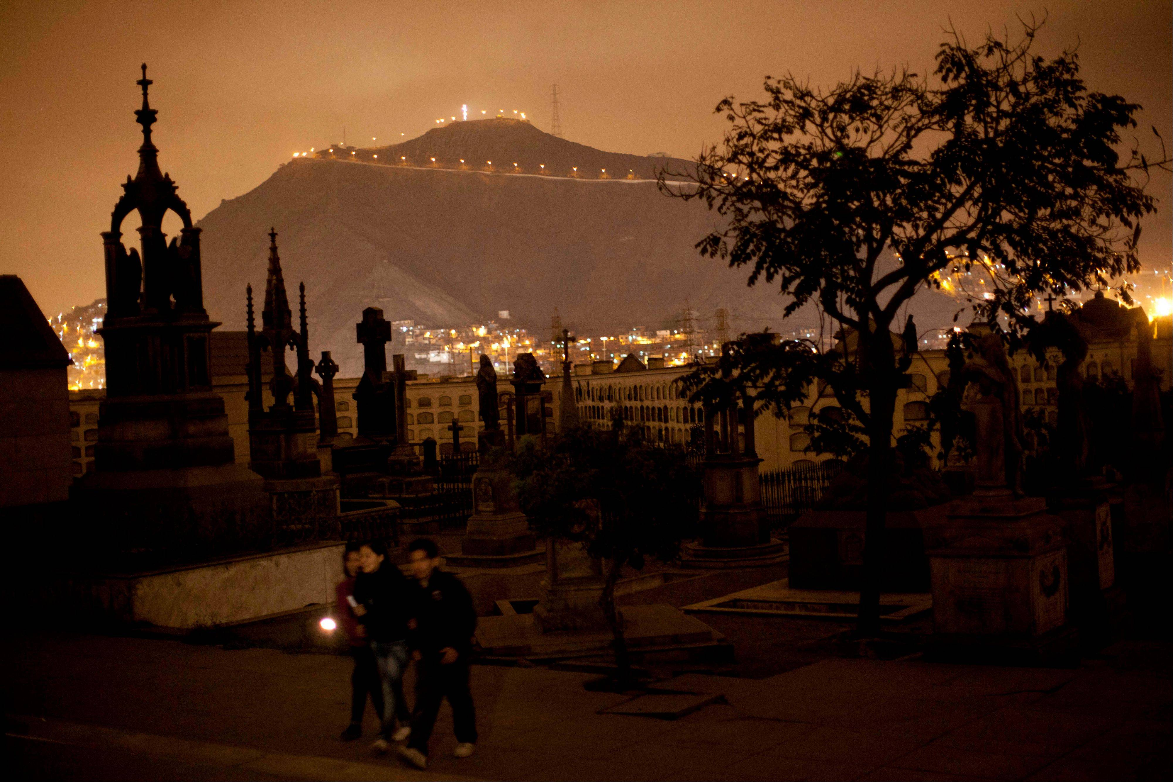 People use a flashlight as they take a nighttime guided tour through the Presbitero Matias Maestro cemetery in Lima, Peru. There are tombs of popular saints the Vatican doesn't recognize.