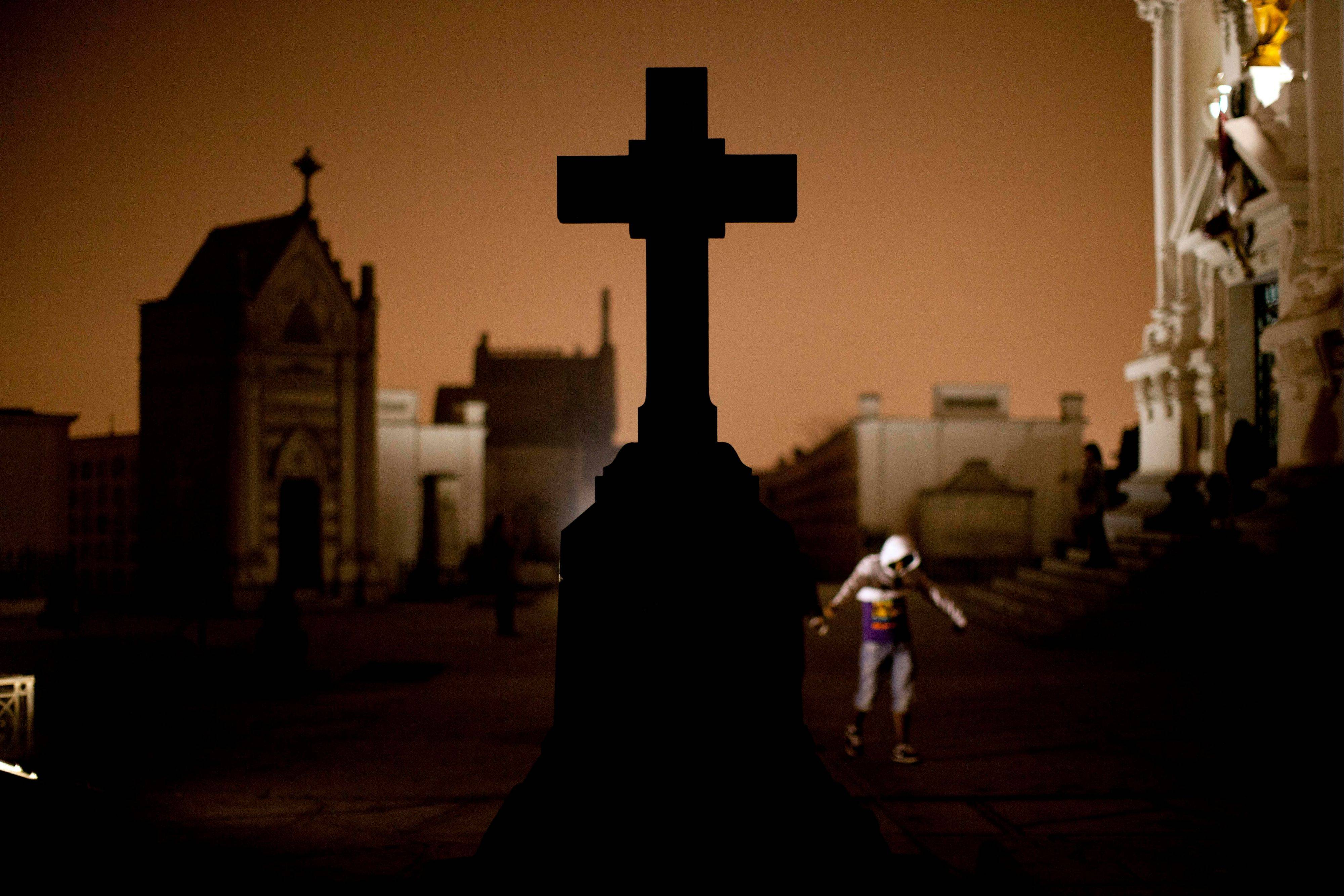 A cross stands in the Presbitero Matias Maestro cemetery during a nighttime guided tour in Lima. The cemetery, created by one of the last Spanish viceroys, was established outside the walls of old Lima.