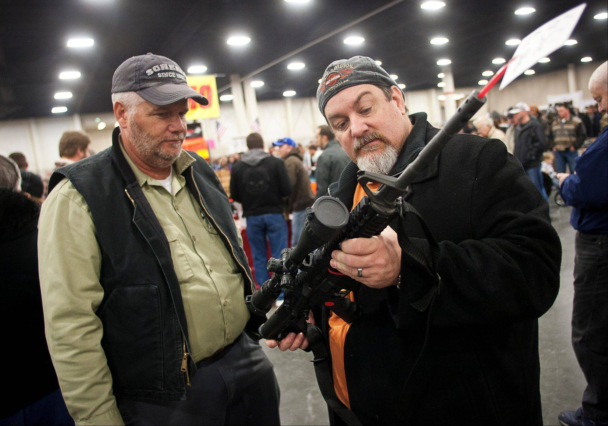 Gun owners discuss a potential sale of an AR-15, one of the most popular and controversial weapons, during the 2013 Rocky Mountain Gun Show at the South Towne Expo Center in Sandy, Utah Saturday. In spite of the recent school shooting in Newtown, Conn., gun enthusiasts packed in by the h