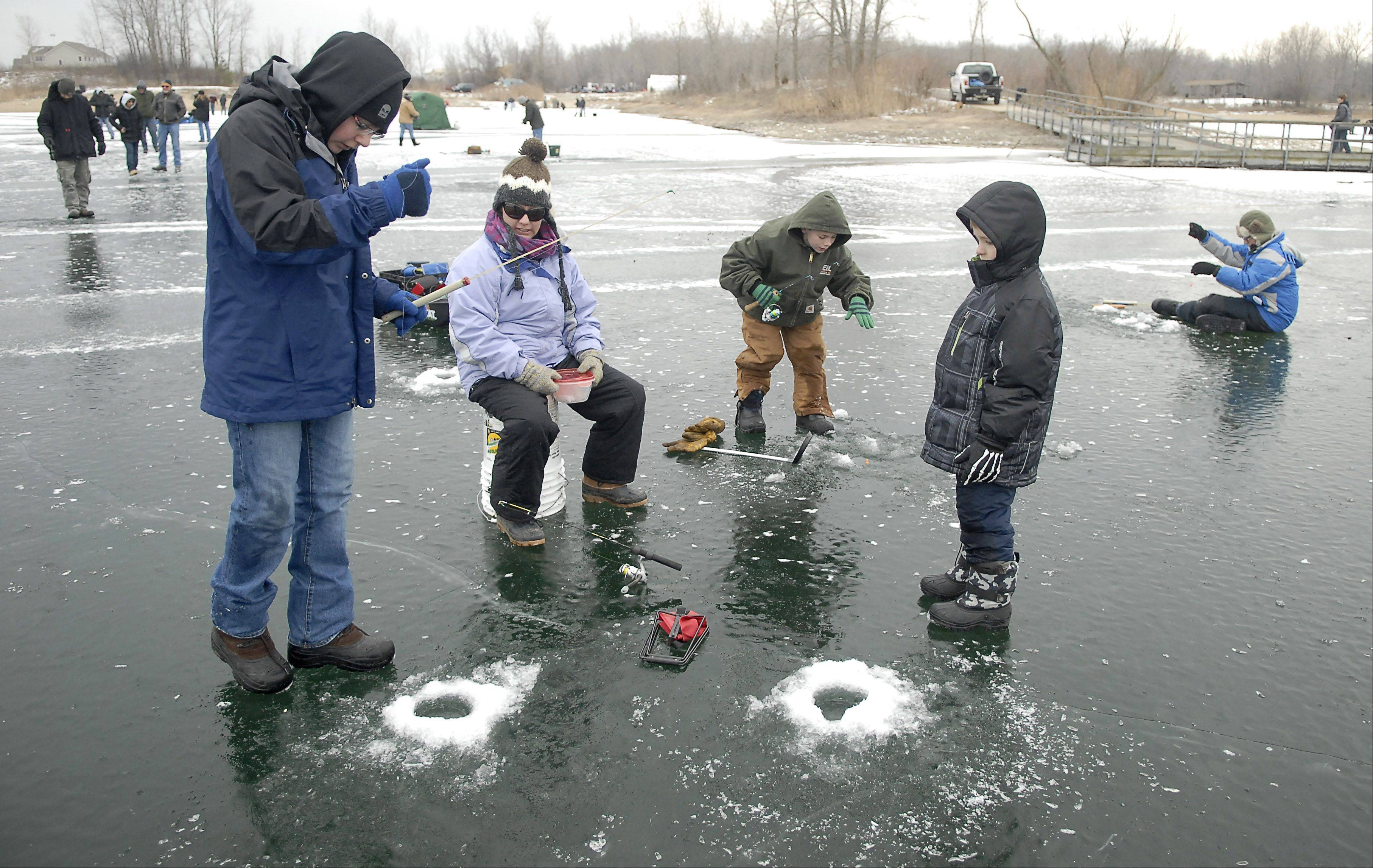 Thomas Gaudio, 15, of Lake in the Hills, left, lowers his line into a fresh hole near Kim Cederlund of Union and her sons, Tyler, 11, center, and 8-year-old Will during Saturday's Frost Fishing Fair in Cary. The event was organized by the McHenry Conservation District.