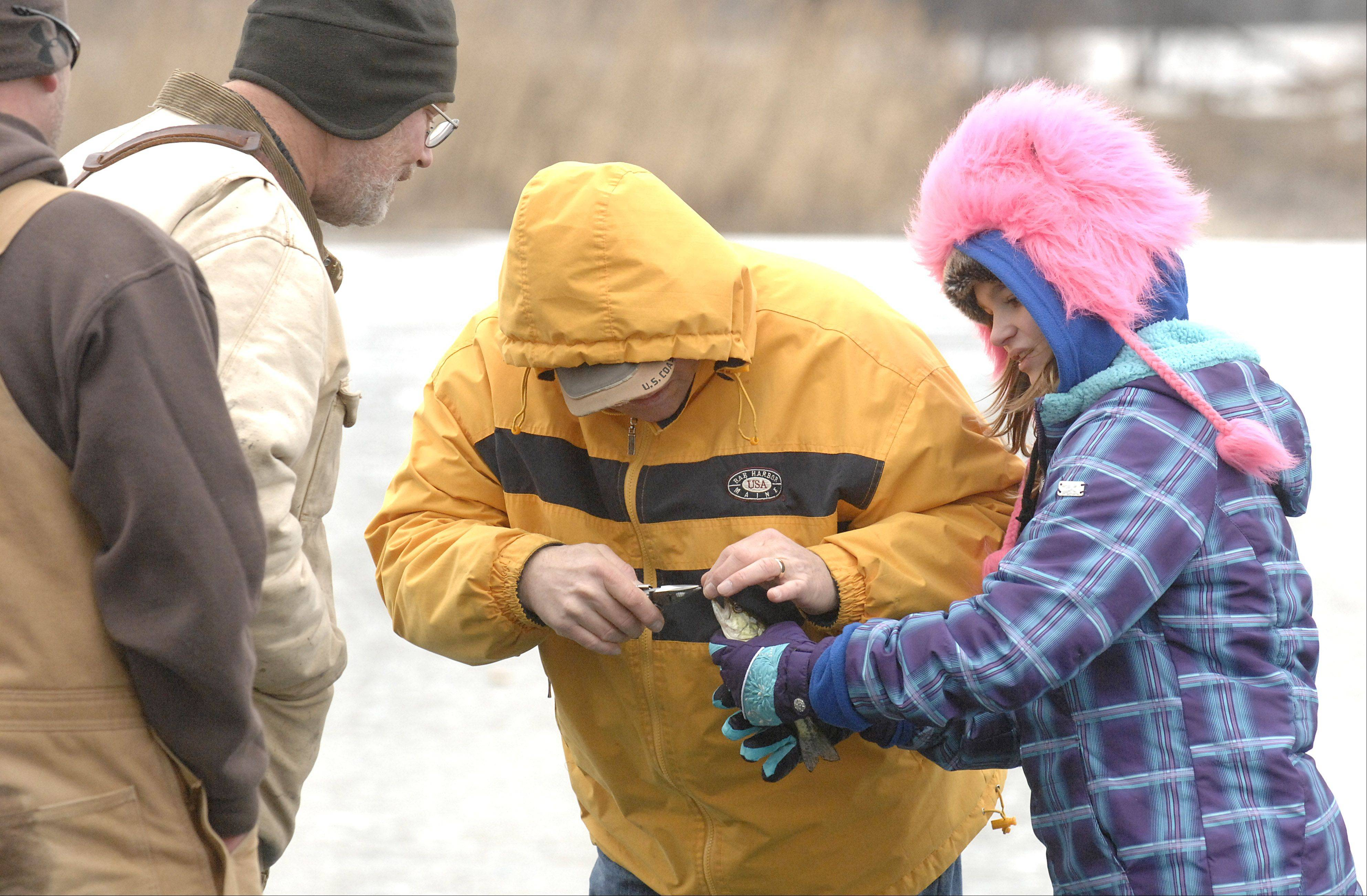 Robert Blass of Lake Zurich helps his granddaughter, Pam McLean, 14, of Wauconda, take a hook out of a fish she caught Saturday during the McHenry Conservation District's Frost Fishing Fair in Cary. They quickly released the fish back into Lake Atwood.