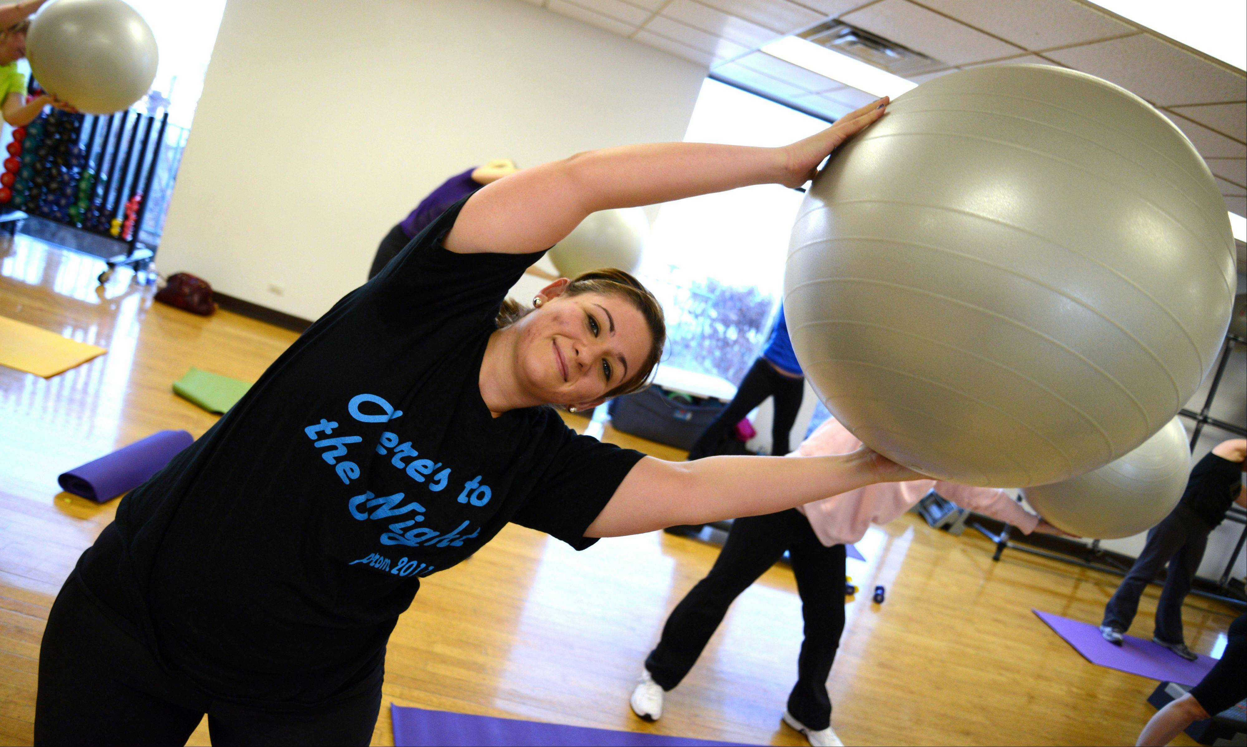 "Rosanna Catapano of Bloomingdale works out with an exercise ball Saturday during Beginner Bootcamp at the Bloomingdale Park District's first Fitness Open House. Catapano said she's ""ready to get back in shape"" in 2013."
