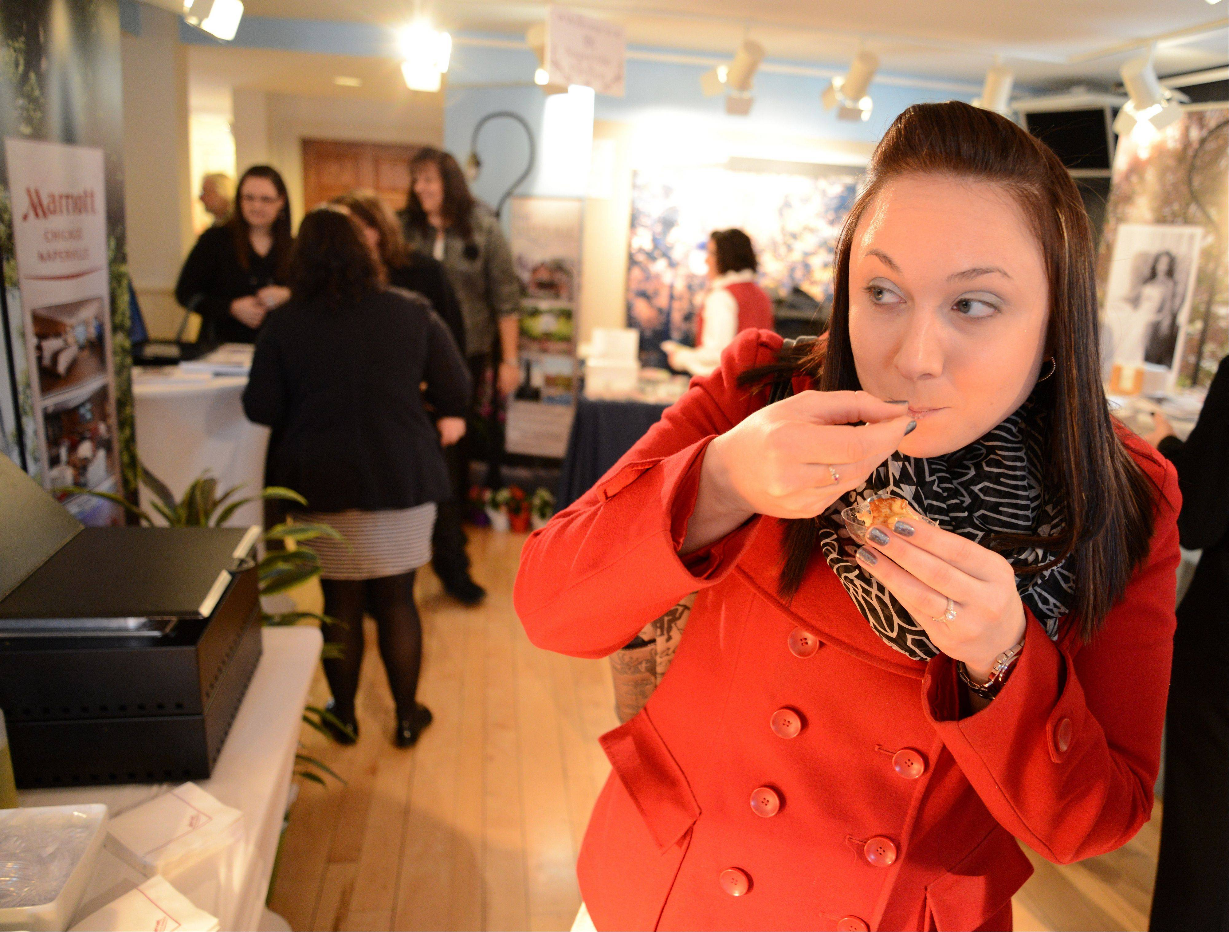 Kristen Price of Naperville samples some crabcake made by the Marriott in Naperville during the Naper Settlement's annual Bridal Showcase. On Saturday, more than 50 vendors had their services on display.