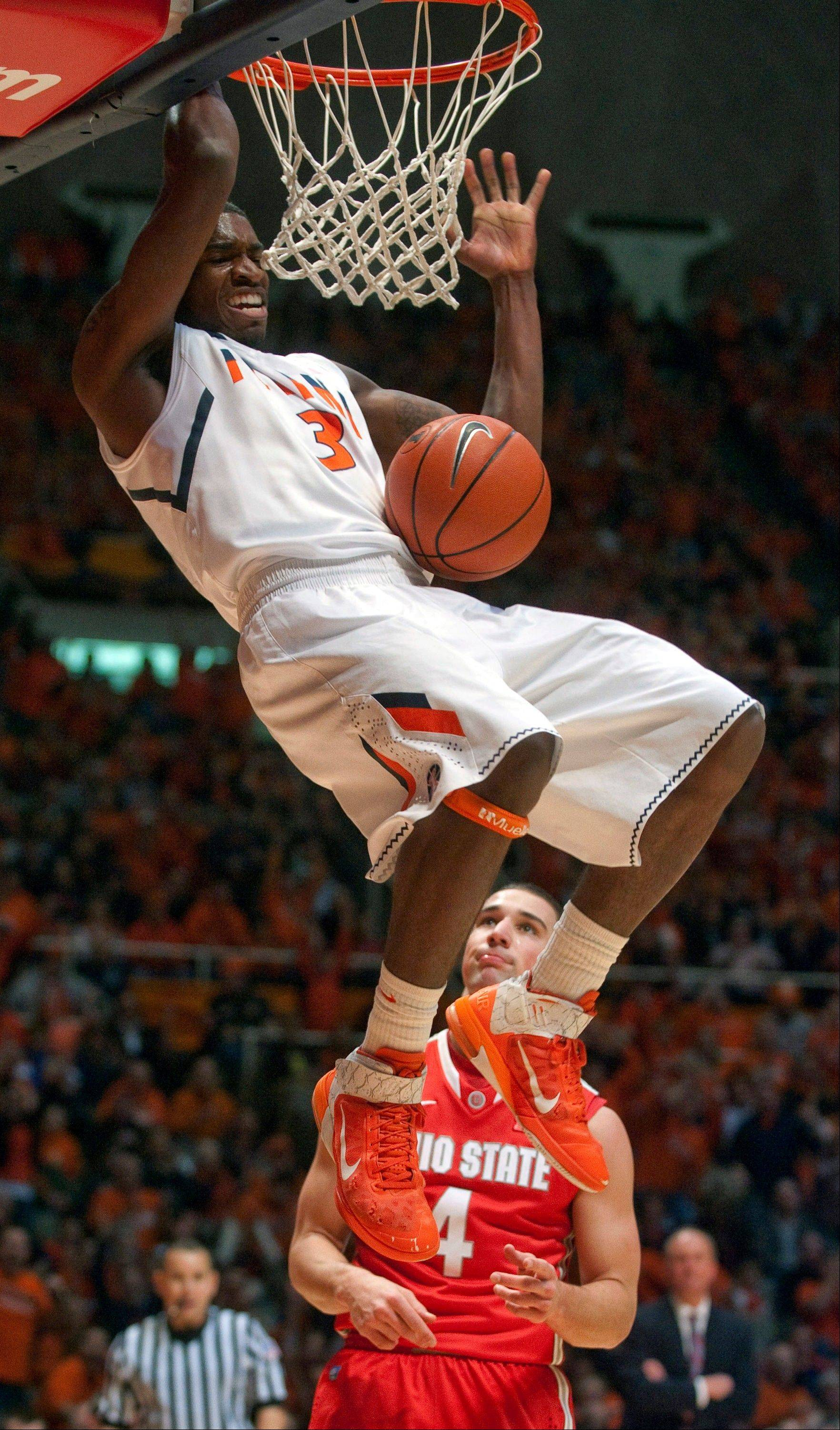 Illinois guard Brandon Paul (3) dunks as Ohio State guard Aaron Craft (4) looks on Saturday during the first half in Champaign.