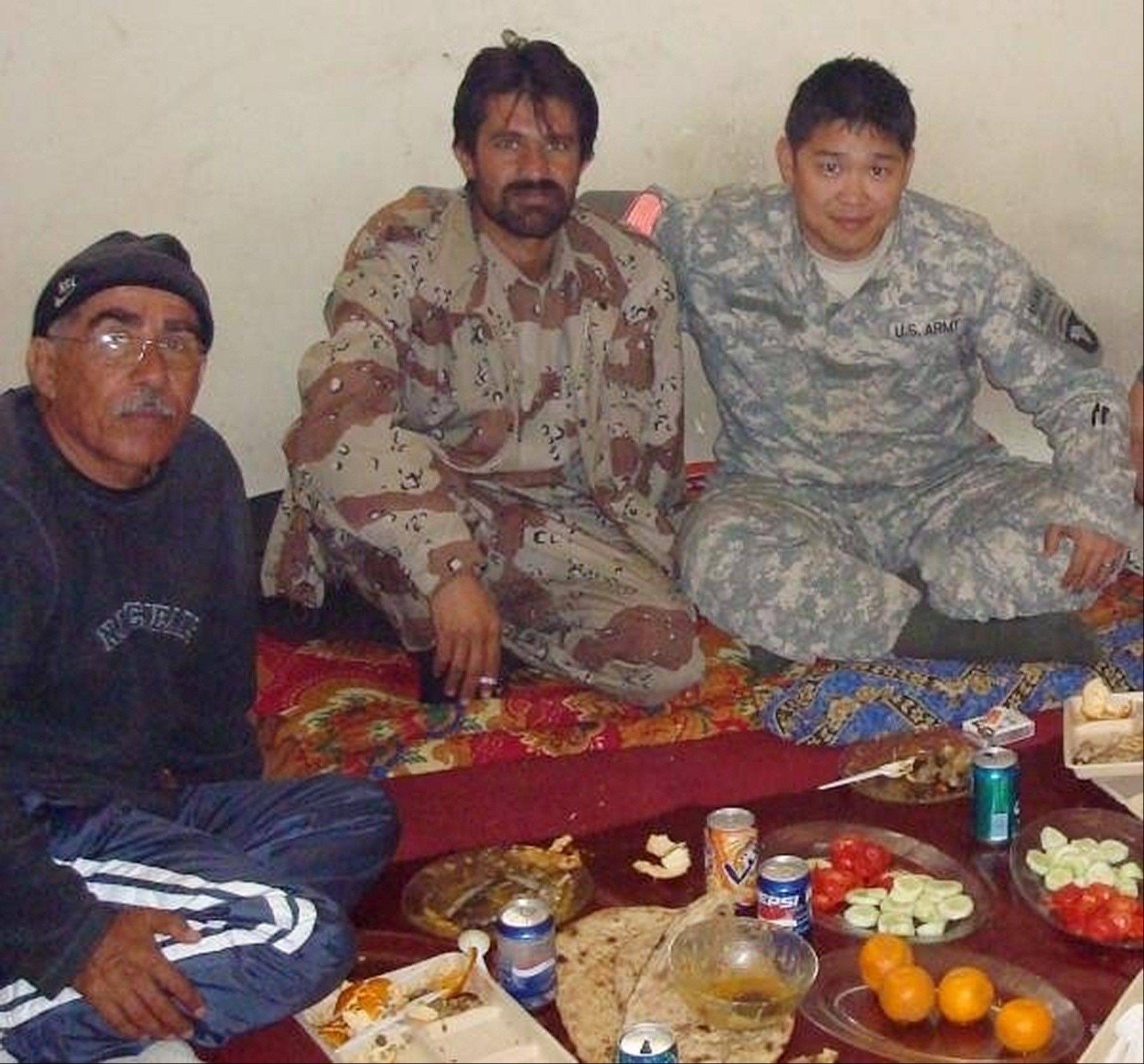 This 2008 photo provided by Stephen Lee shows him, right, having a meal with Afghans in Paktika province, Afghanistan. Lee was still in Afghanistan — his second deployment to the war zone — when he began looking at colleges. The California native settled on the University of Wisconsin-Madison and had already begun his studies when he learned of the coming changes to his GI Bill benefits. He was looking at an extra $20,000 a year out of pocket.