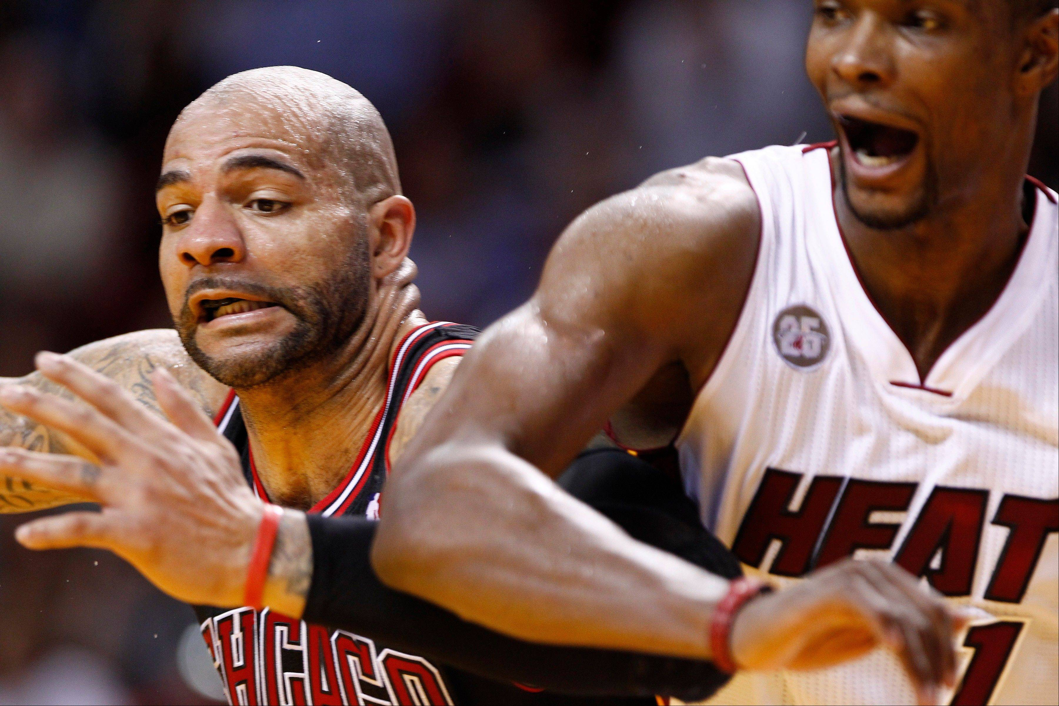 The Bulls' Carlos Boozer and the Heat's Chris Bosh battle for the ball during the second half Friday night in Miami.