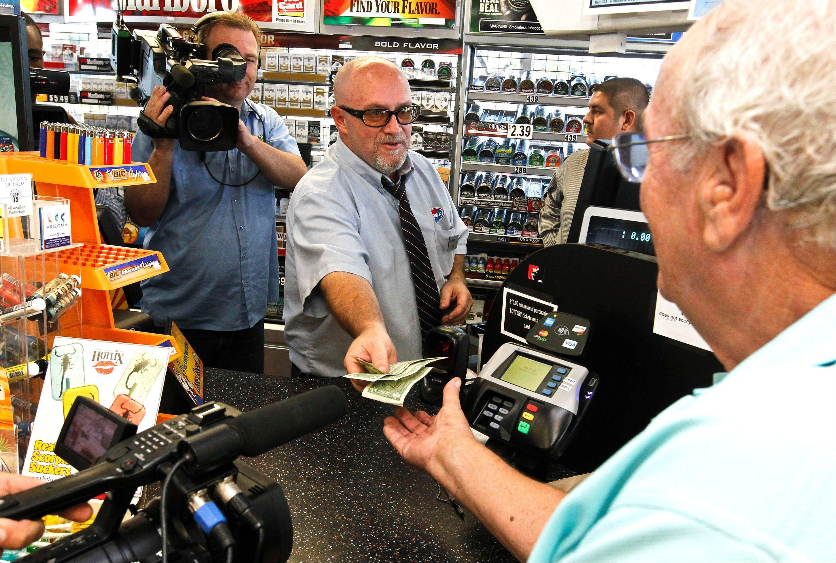 Television cameras roll as store manager Bob Chebat, middle, hands over Wes Prinzen's, right, modest $4 winnings, at a 4 Sons Food Store where one of the winning tickets in the $579.9 million Powerball jackpot was purchased in Fountain Hills, Ariz. When two winning tickets for a record Powerball jackpot were claimed last month, the world focused on the winners. One, from Missouri, showed up at the news conference, while the other, in Arizona, chose to remain anonymous. Releasing information on the lottery winners reflects a broader debate playing out in state Legislatures and lottery offices nationwide: Should the winners' names be made public?