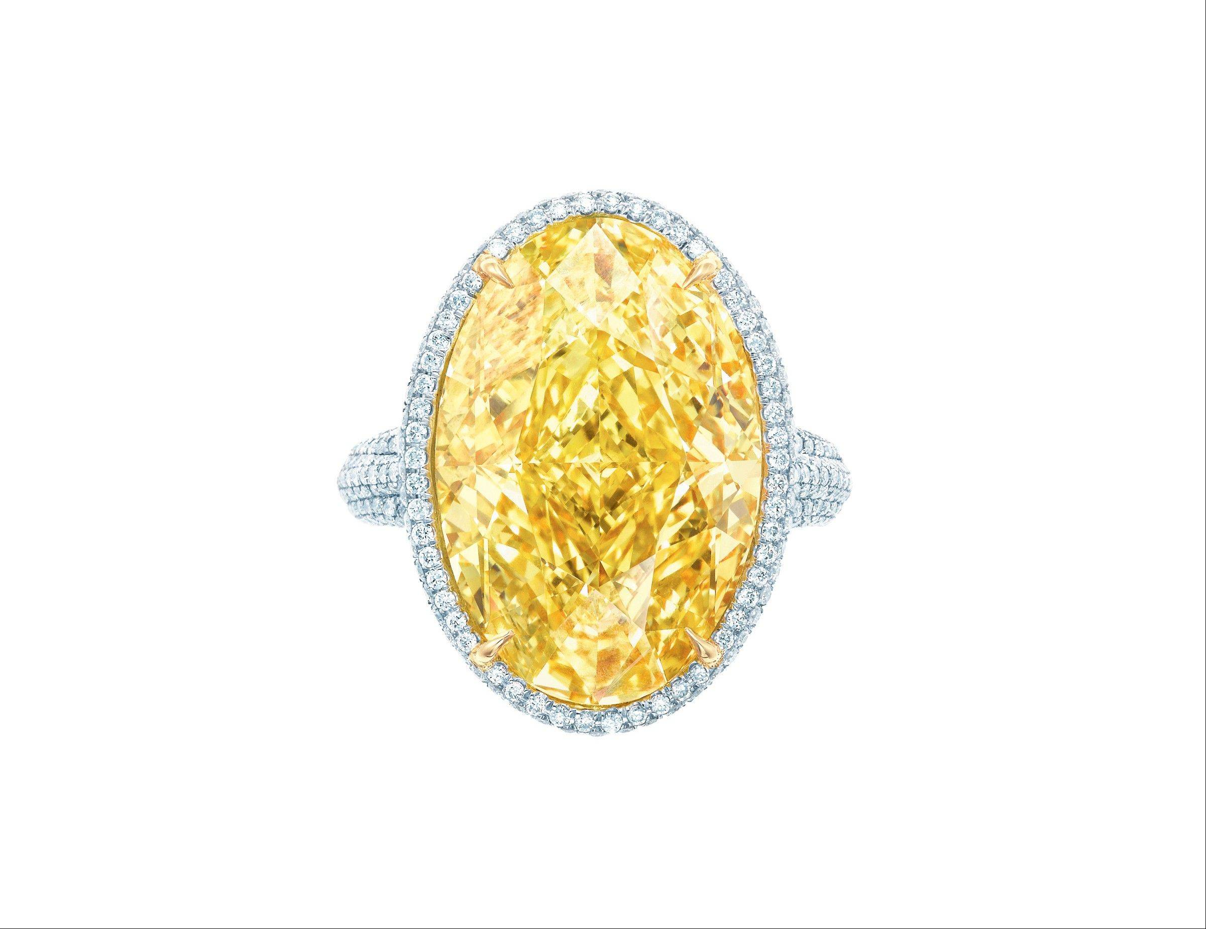 A 15-carat oval fancy vivid yellow diamond ring with white diamonds and set in platinum and 18-carat yellow gold.