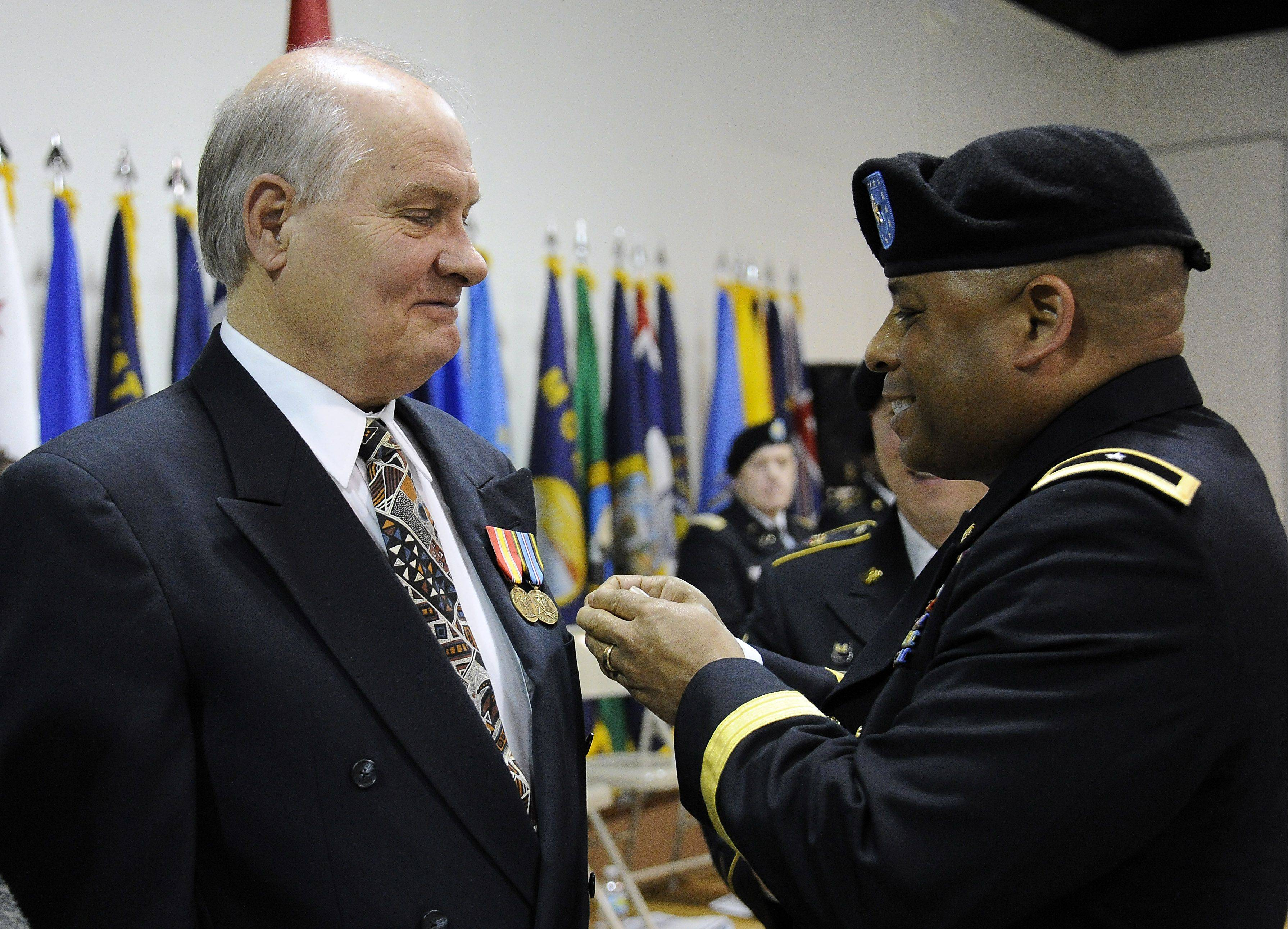 Brig. Gen. Gracus Dunn of the 85th support Command pins medals on Gary Roberts, 71, of Arlington Heights that he earned for his service 47 years ago in the Dominican Republic. The ceremony was Saturday at the U.S. Army Reserve Training Center in Arlington Heights.